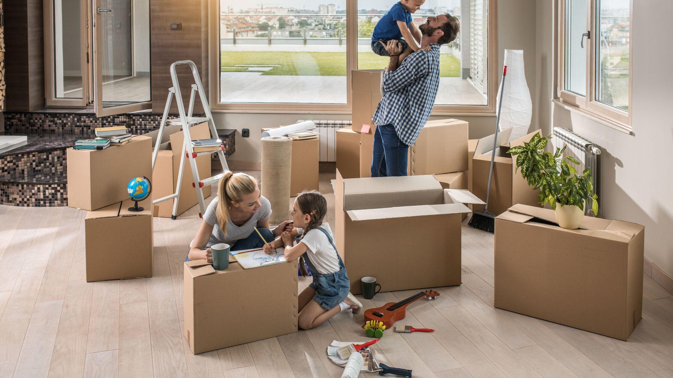 Eltern und zwei Kinder zwischen Umzugskisten im Wohnzimmer.