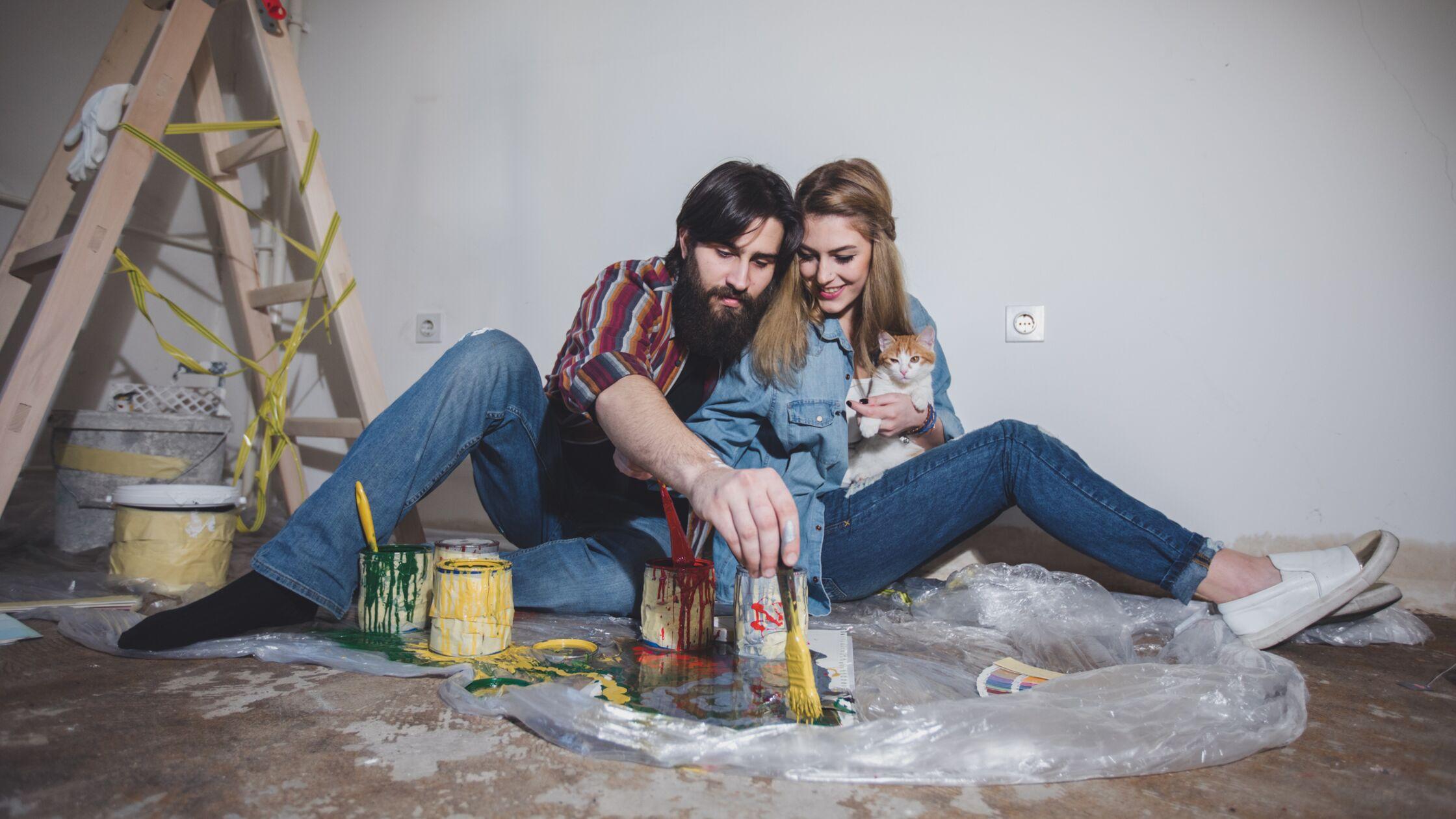 Mann und Frau in neuer Wohnung mischen Farben, Frau mit junger Katze im Arm
