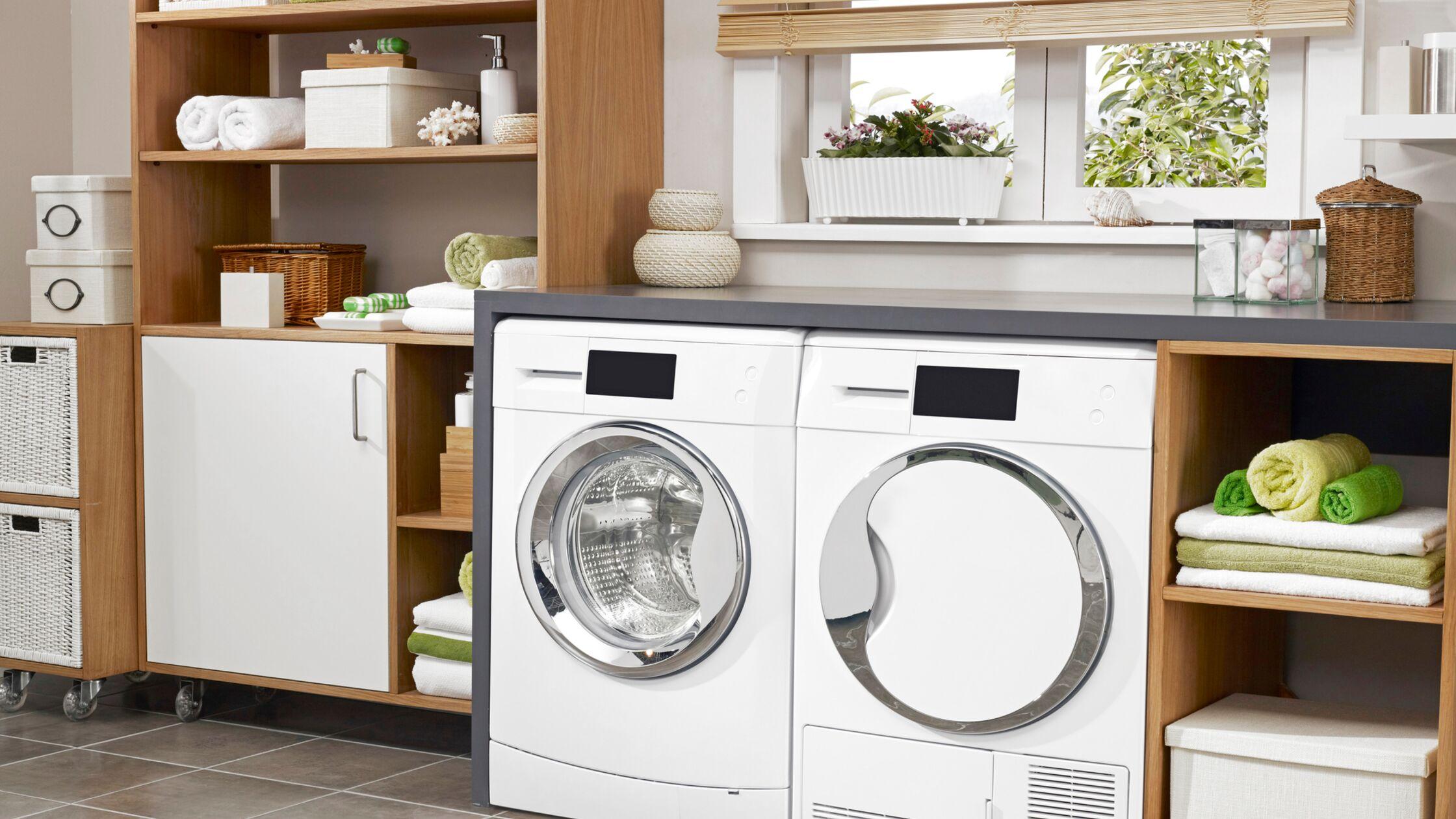 Waschmaschine und Trockner inmitten von Badezimmermöbeln auf Kachelboden.