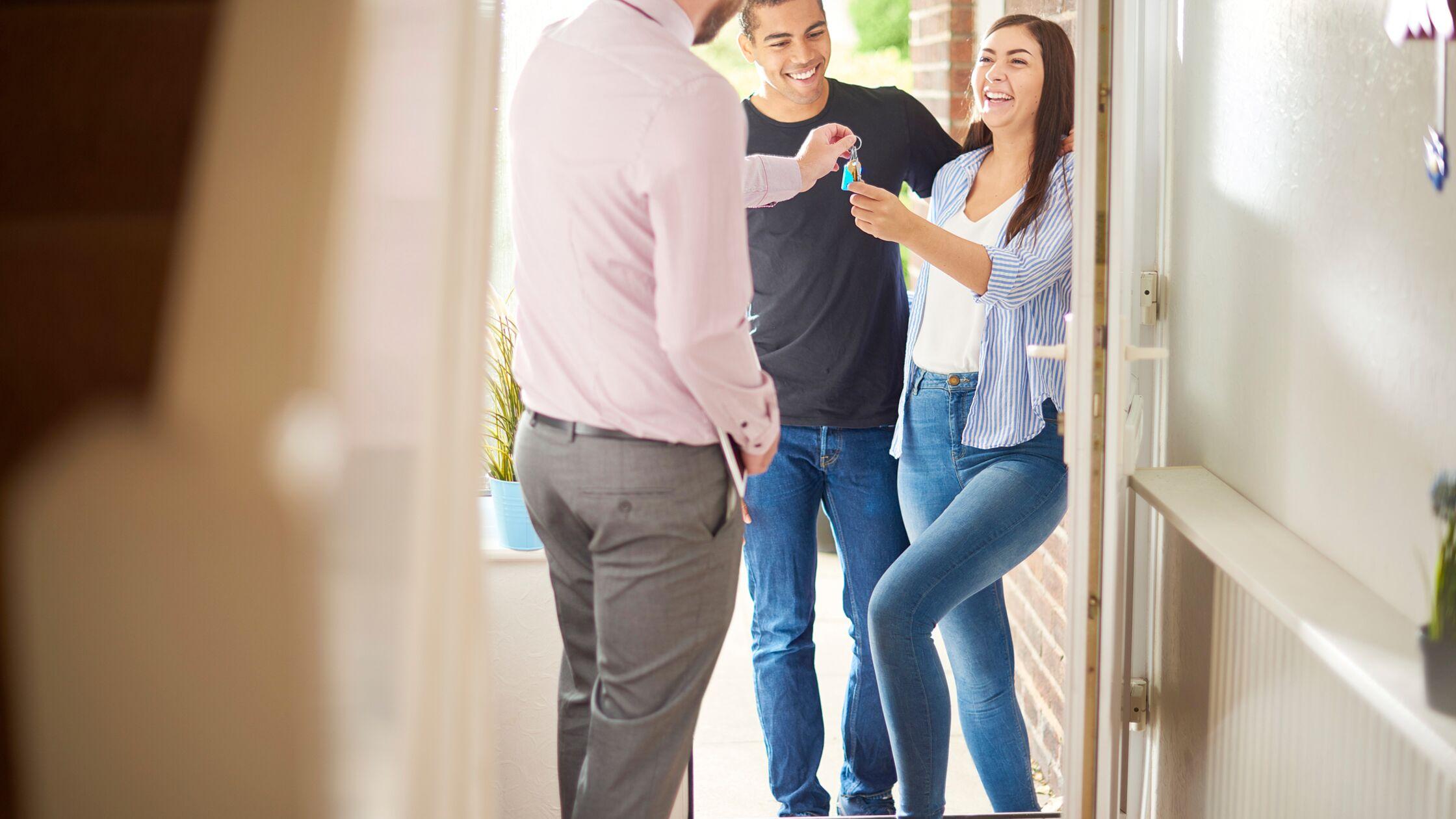 Junges Paar mit Vermieter bei der Schlüsselübergabe