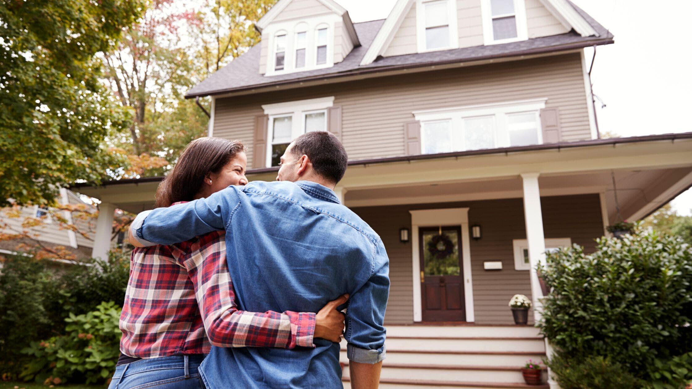 Glückliches Paar vor dem eigenen Haus