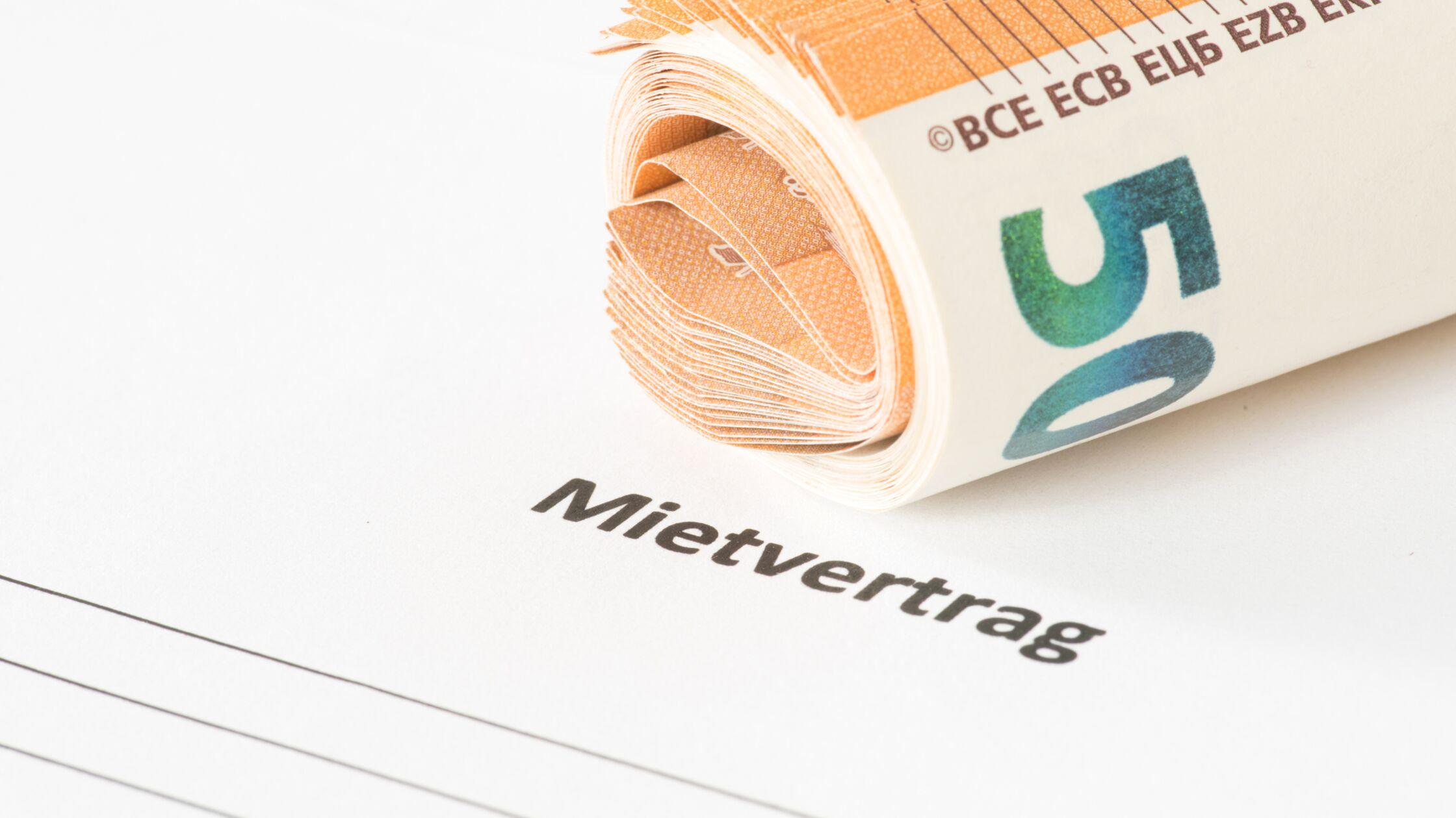 Zusammengerollte Geldscheine liegen auf einem Mietvertrag