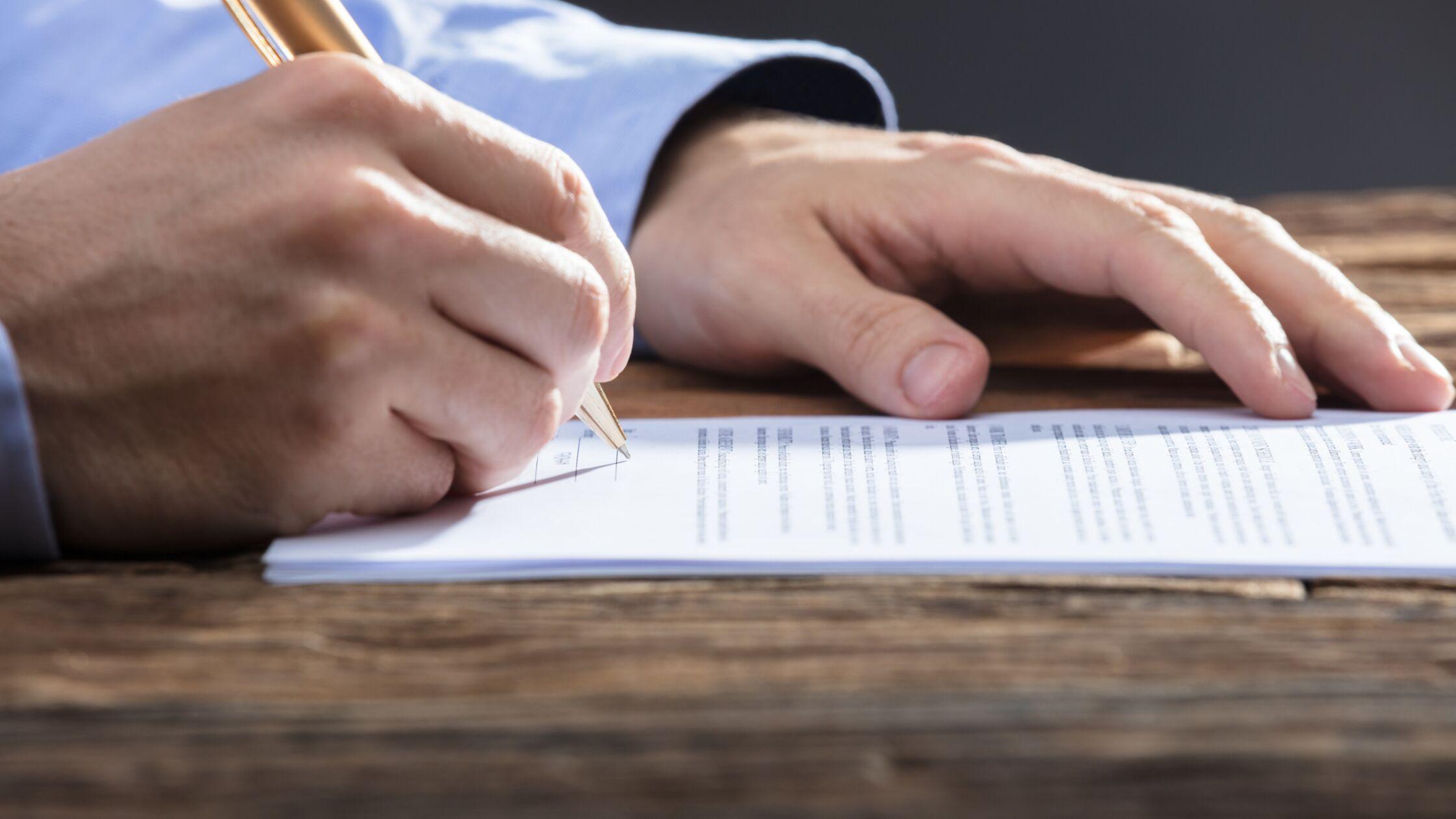 Rechte Hand hält Stift und unterzeichnet Dokument, linke Hand liegt auf dem Schreibtisch
