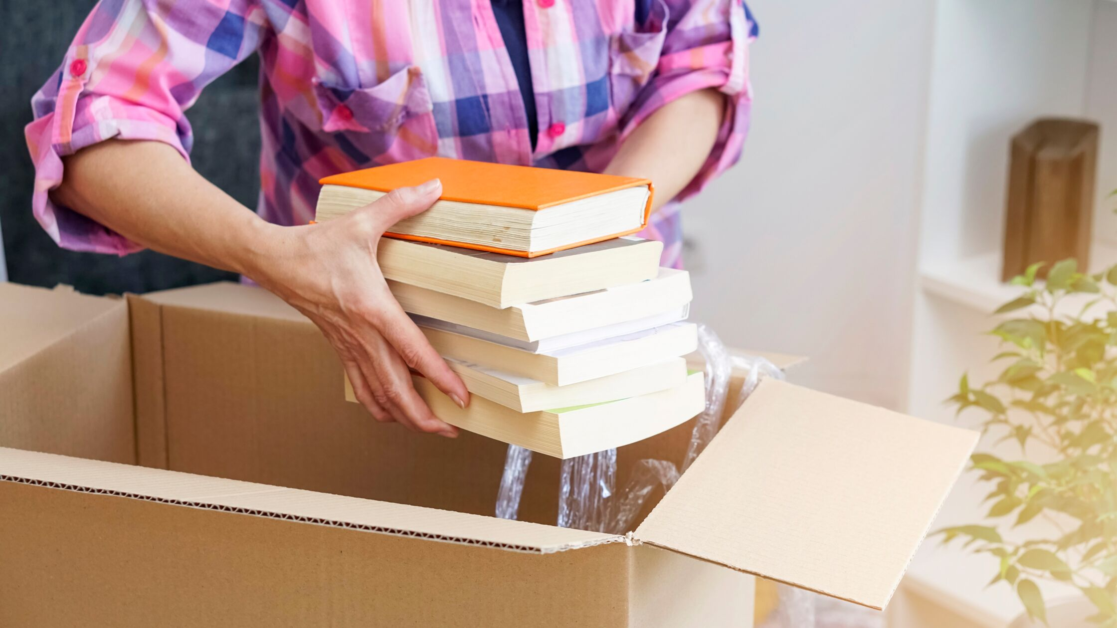 Frau packt Bücher in Umzugskarton.