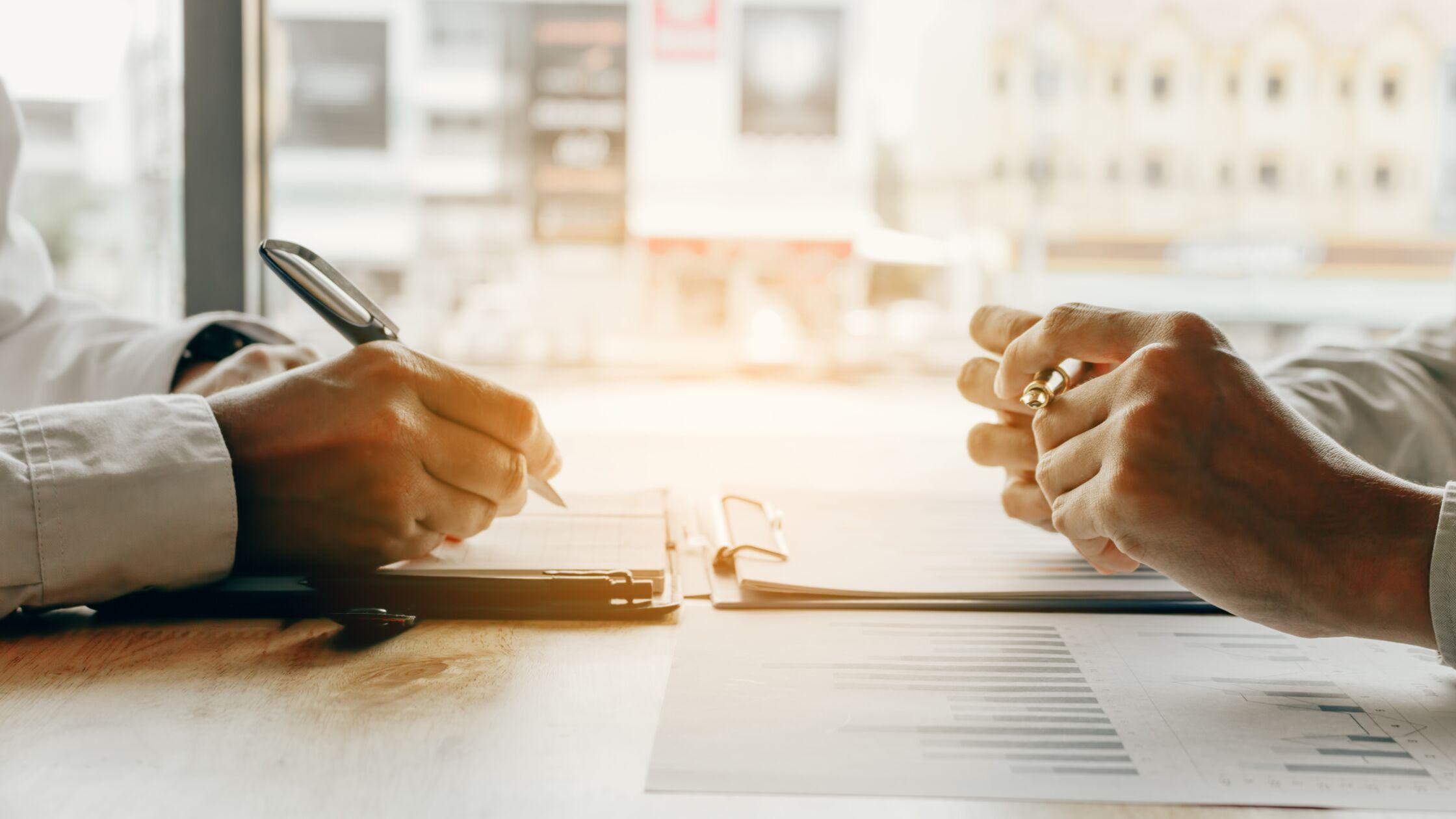 Zwei Paar Hände, Close-up, mit Stiften und Unterlagen