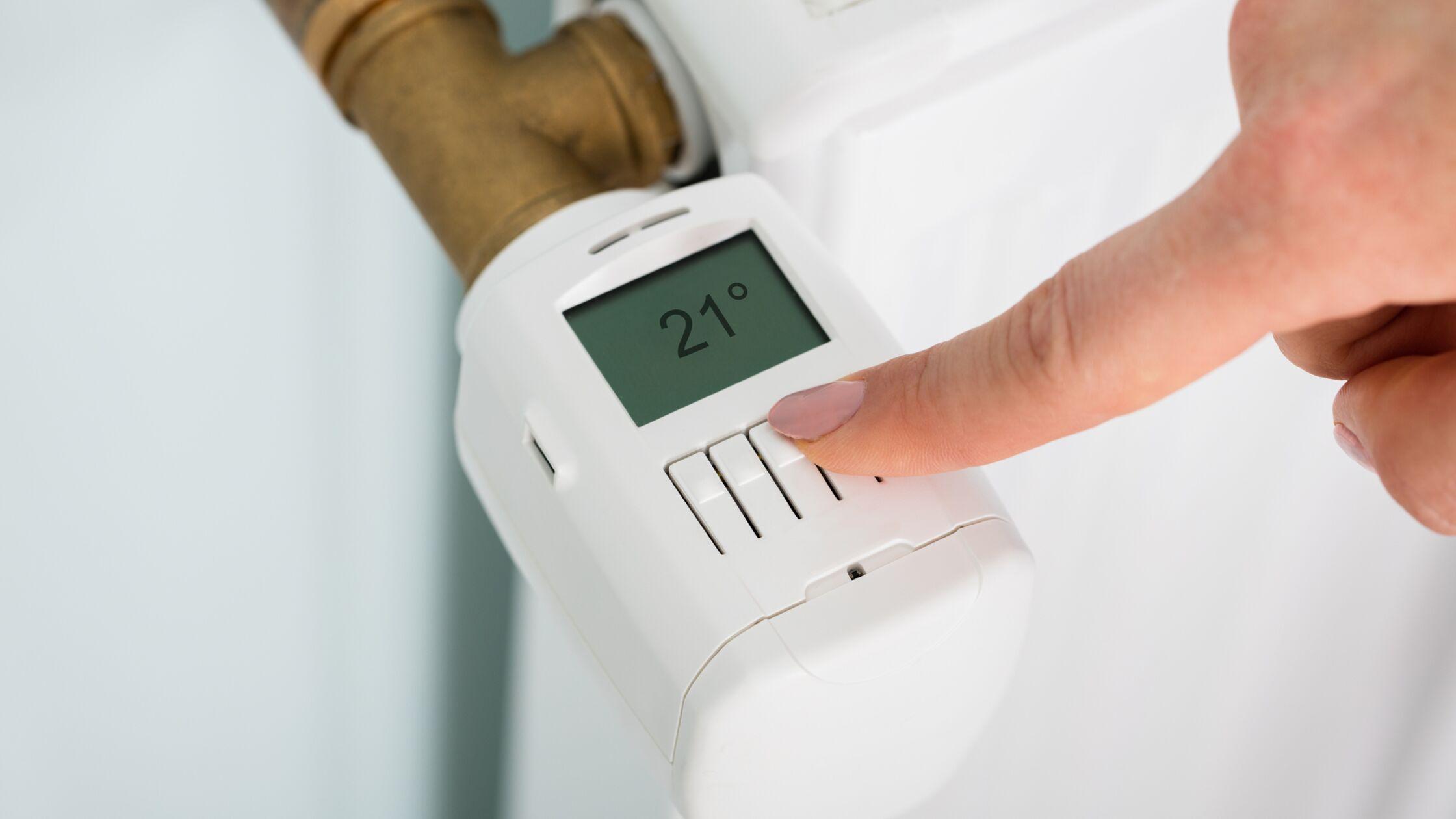 Hand mit Thermostat an einem Heizkörper, der 21°C anzeigt