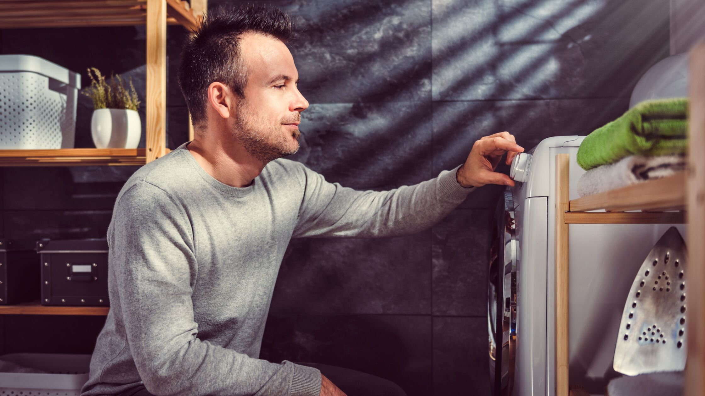 Mann kniet vor einer Waschmaschine und stellt Temperatur ein.