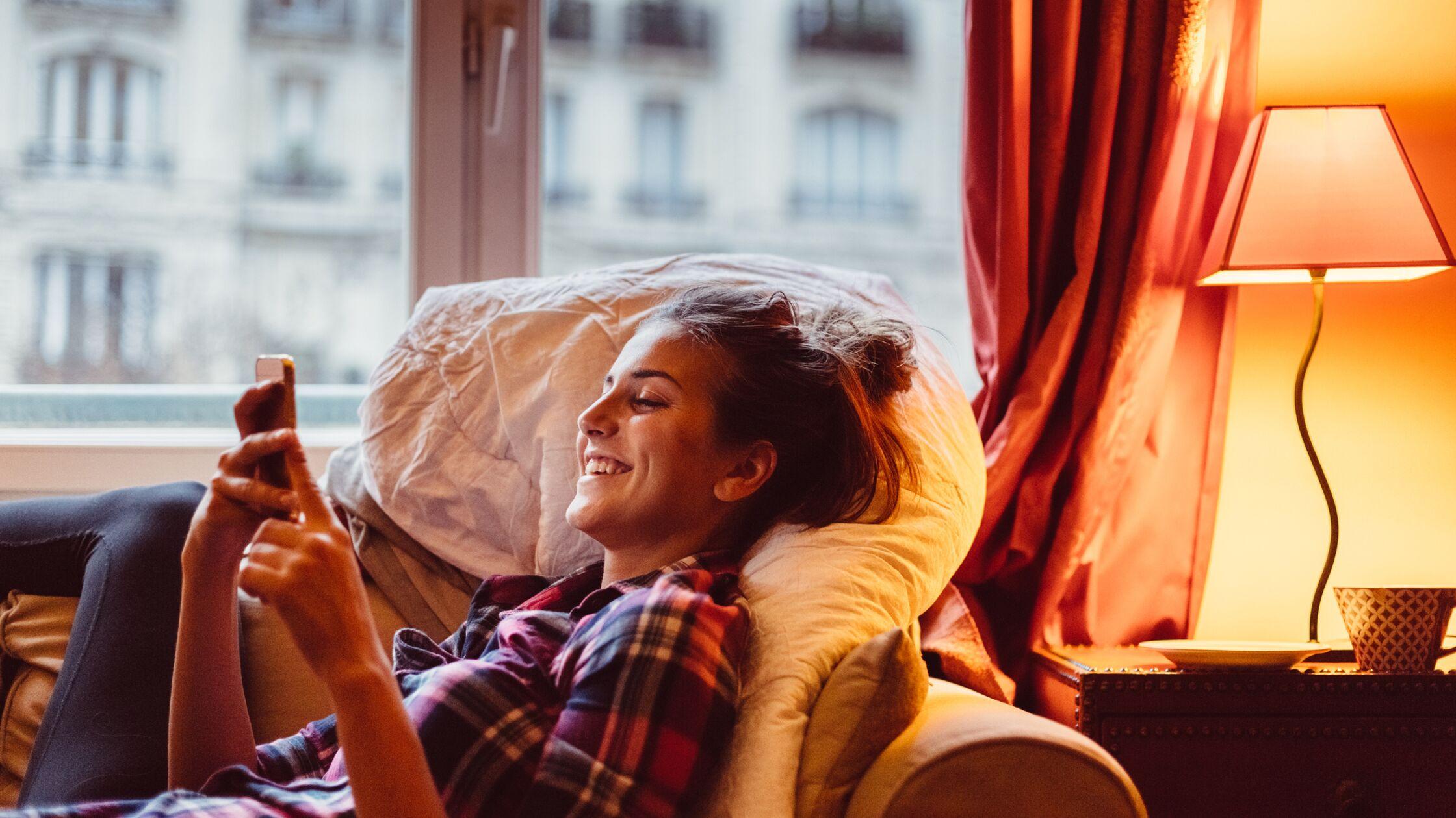 Junge Frau liegt auf dem Sofa und schaut auf ihr Smartphone, hinter ihr brennt eine Lampe