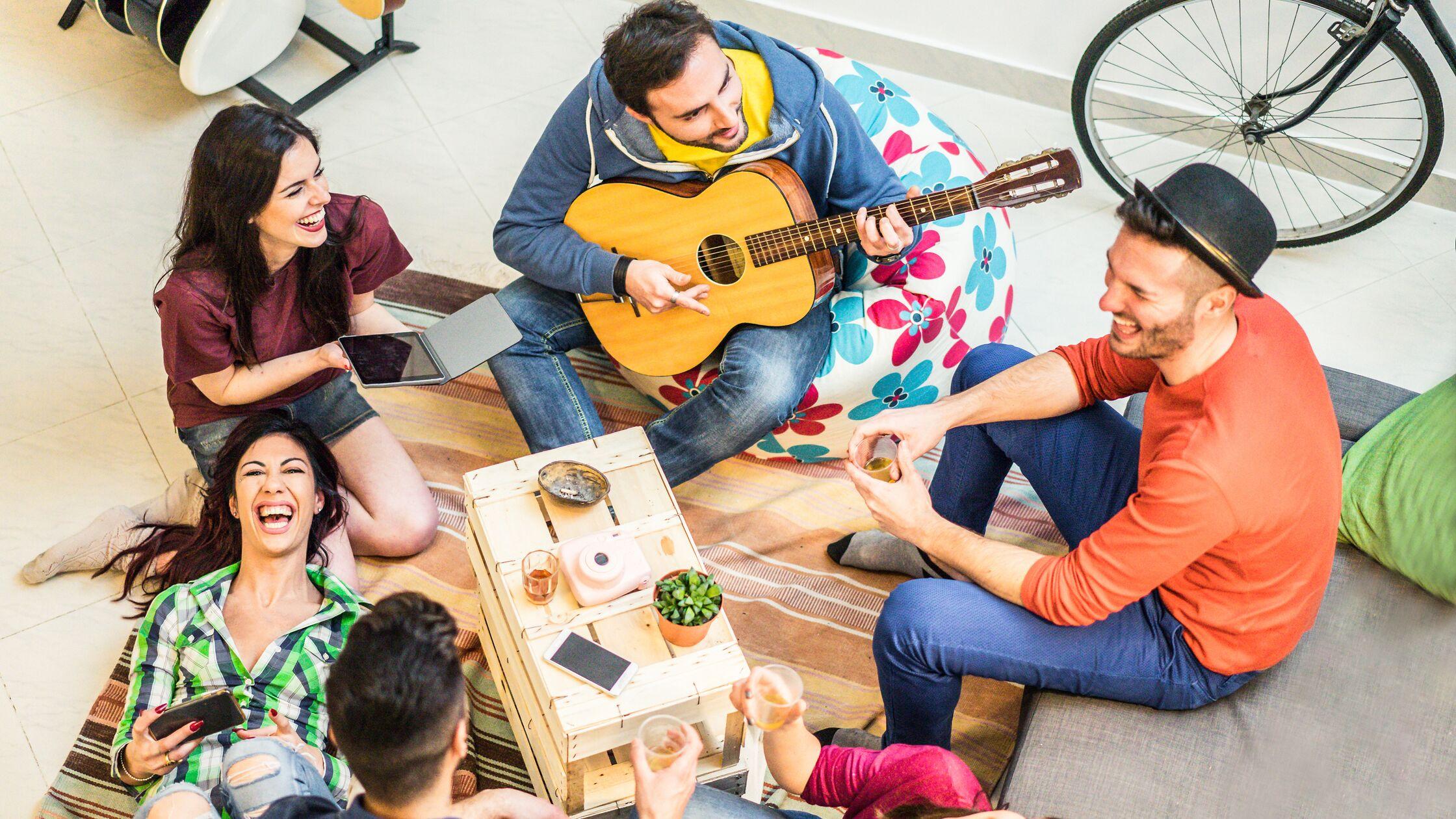 Gruppe junger Leute sitzt auf dem Boden einer Wohnung, lacht und macht Musik