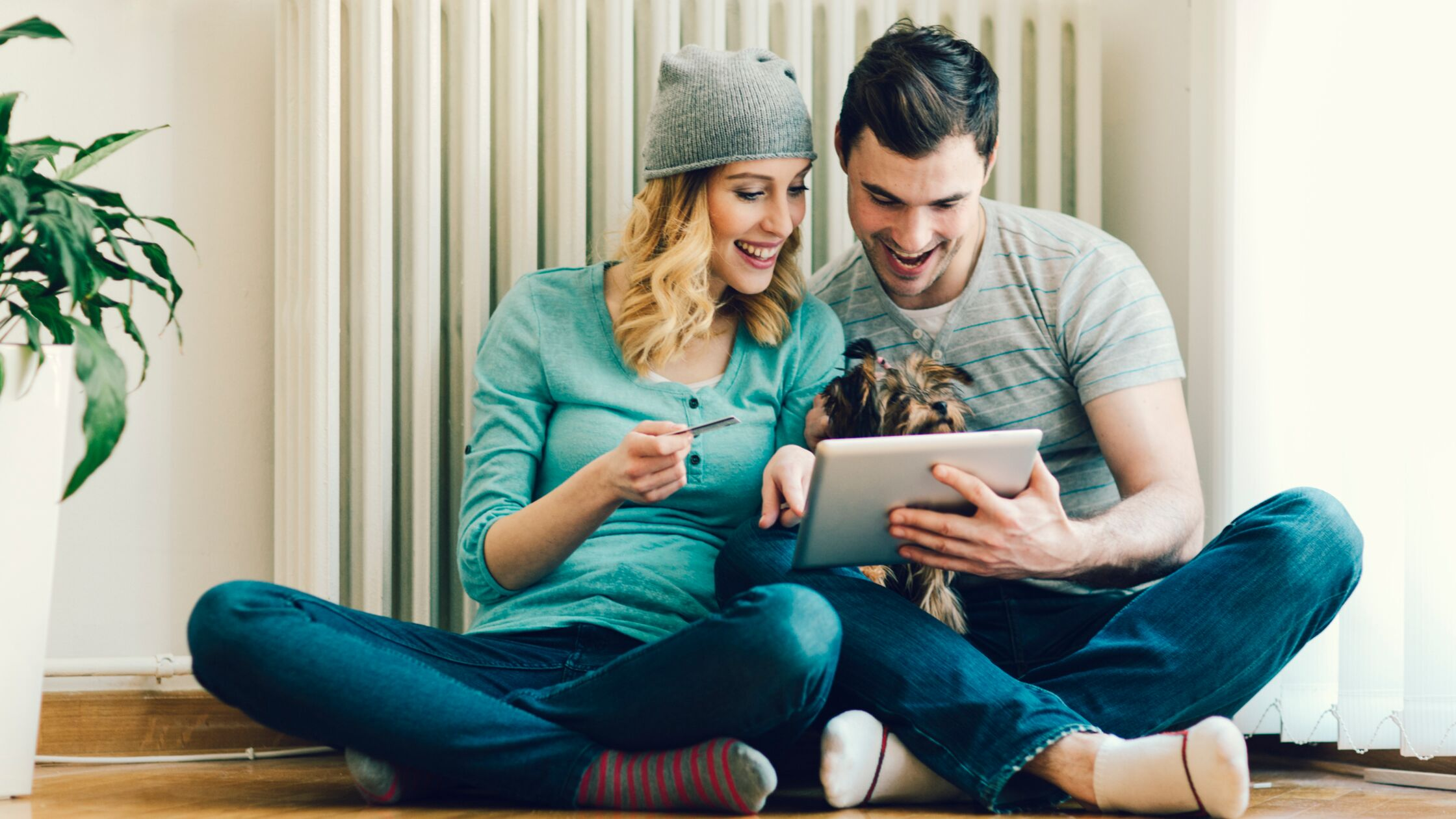 Junges Paar sitzt mit Tablet-PC vor einem Heizkörper