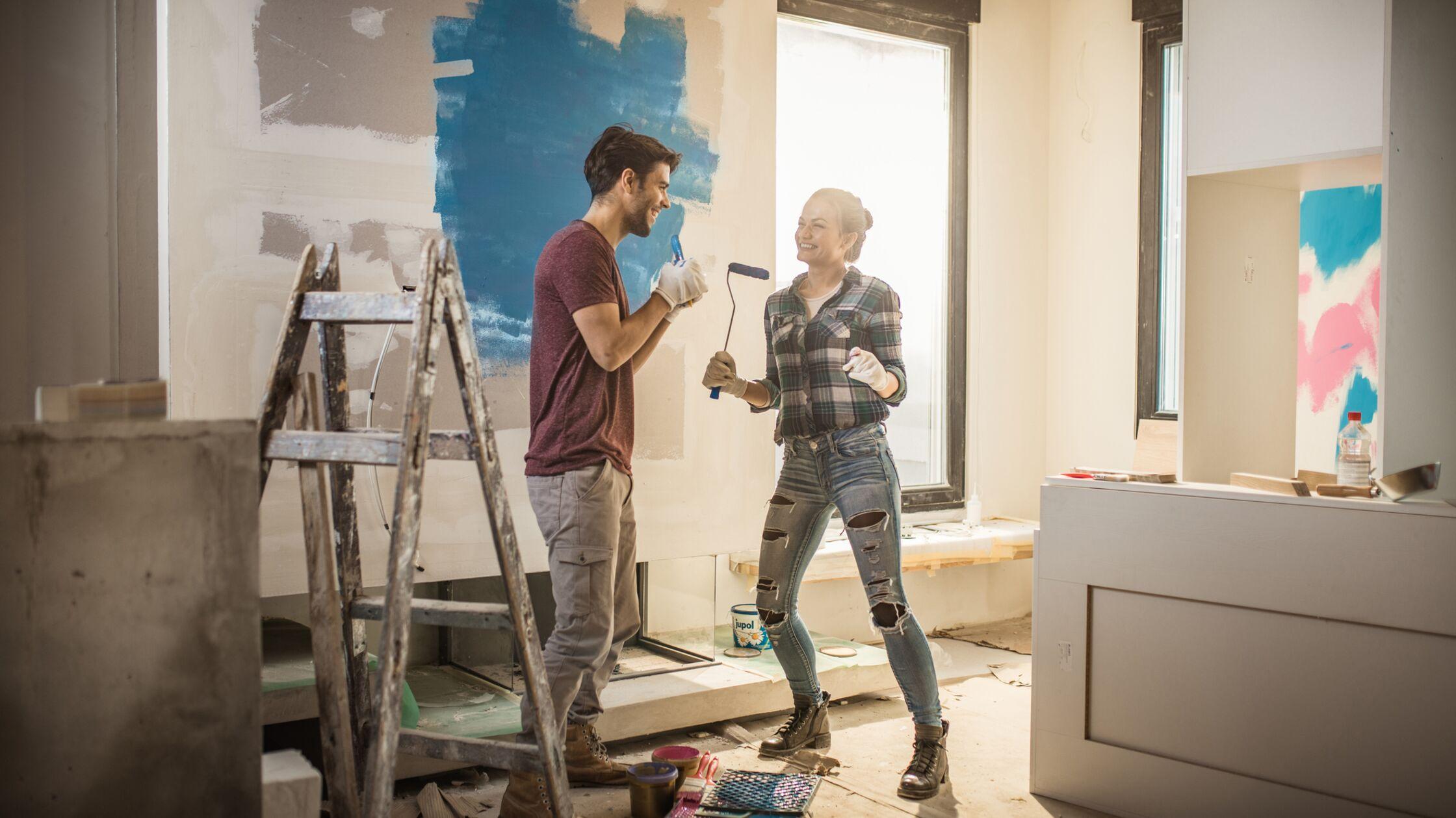 Glückliches Paar streicht Wände in der neuen Wohnung