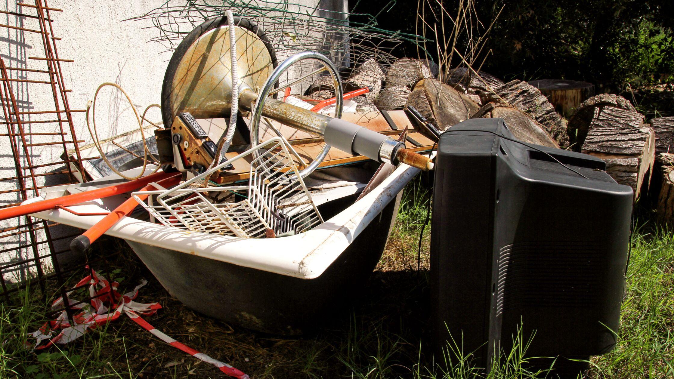 Metallschrott in einer alten Badewanne und ein Röhrenfernseher auf einer Wiese