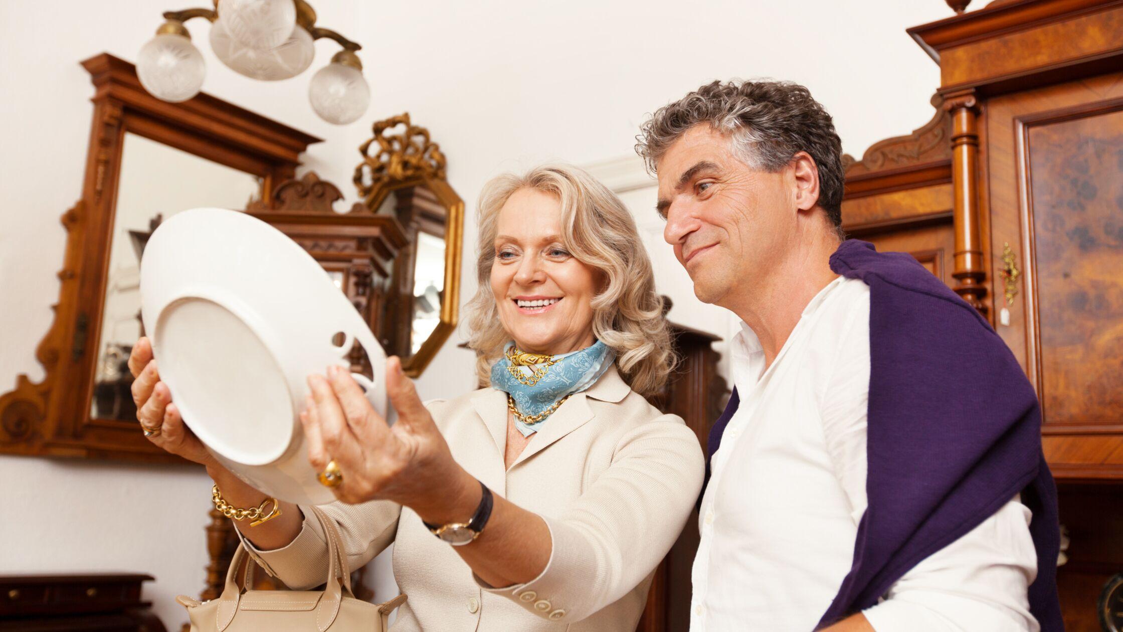 Älteres, reiches Ehepaar mit antiken Möbeln und teurem Porzellan