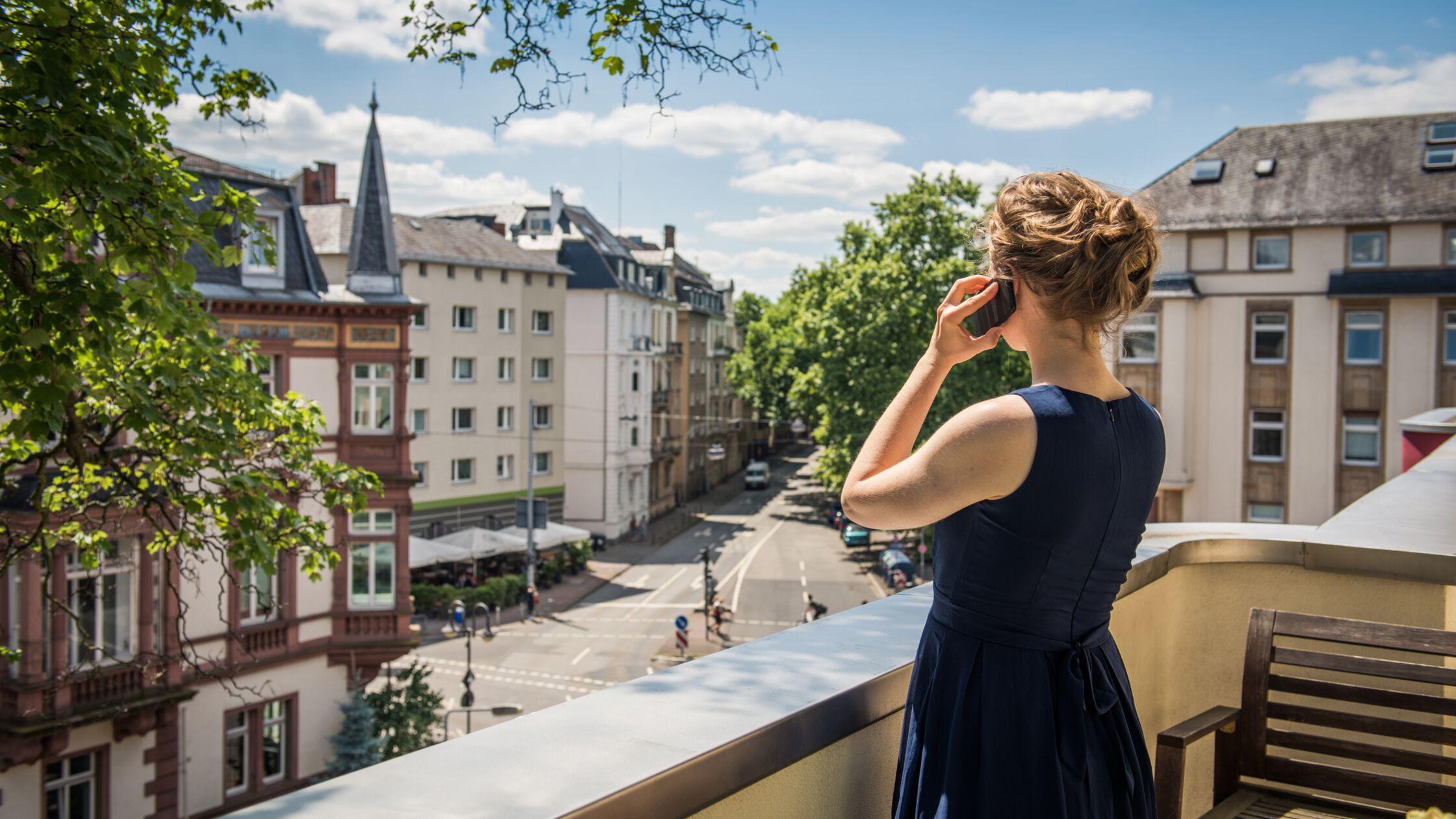 Junge Frau telefoniert auf dem Balkon