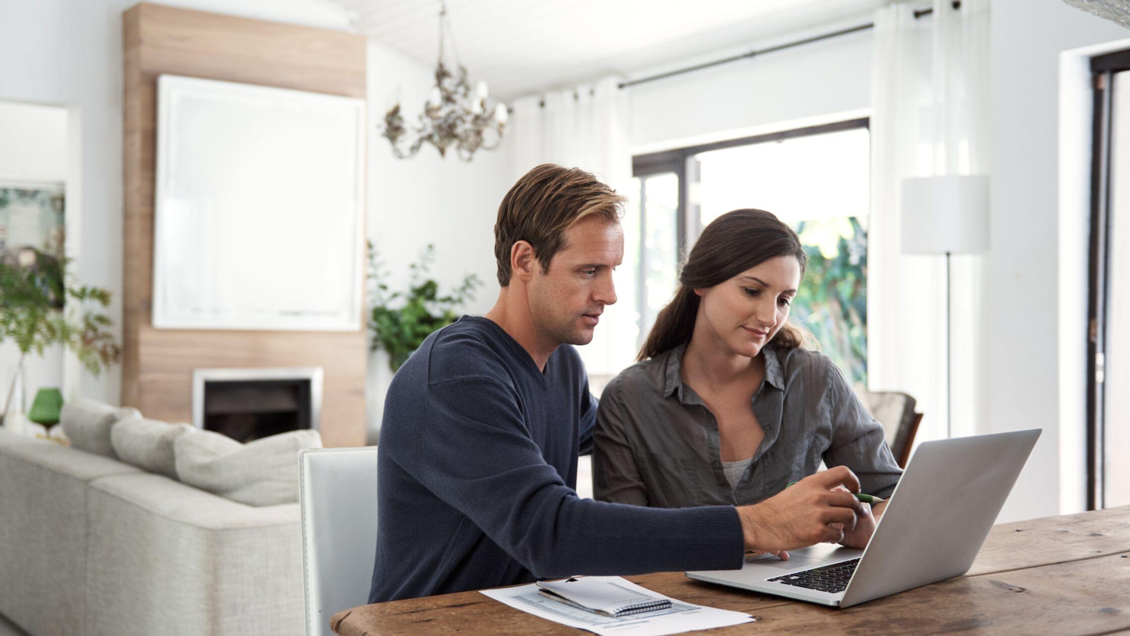 Paar sitzt vor PC mit Papieren und will sich vor Umzug ummelden