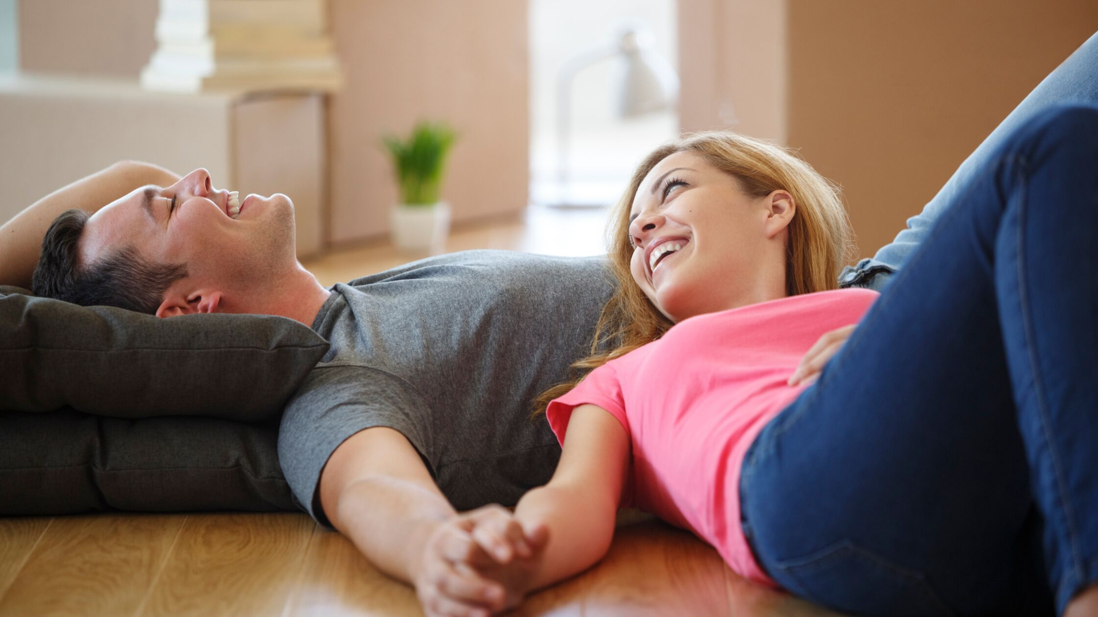 Junges Paar liegt erschöpft und lächelnd auf dem Fußboden der neuen Wohnung.