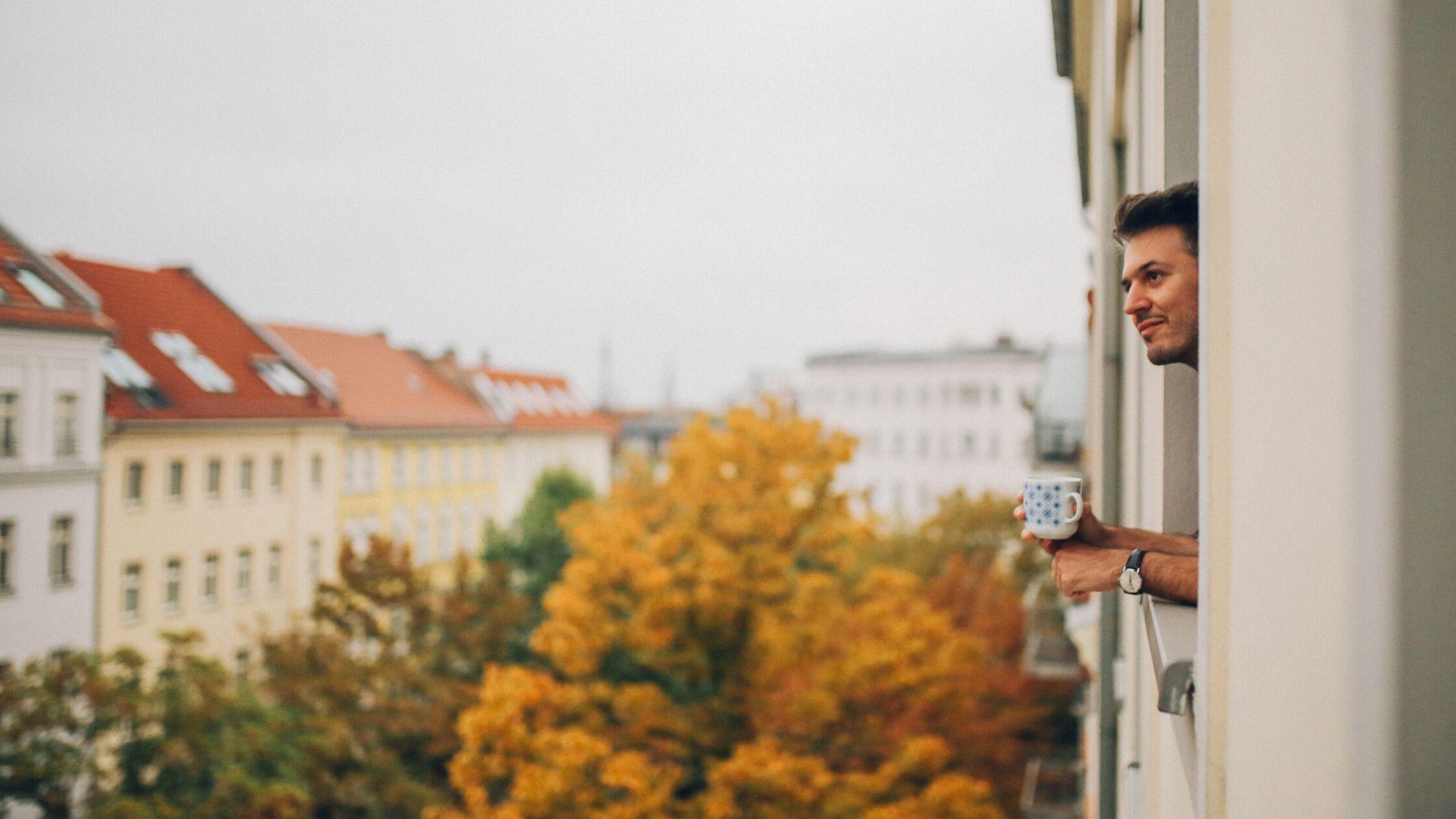 Junger Mann schaut aus dem Fenster eines größeren Wohnhauses