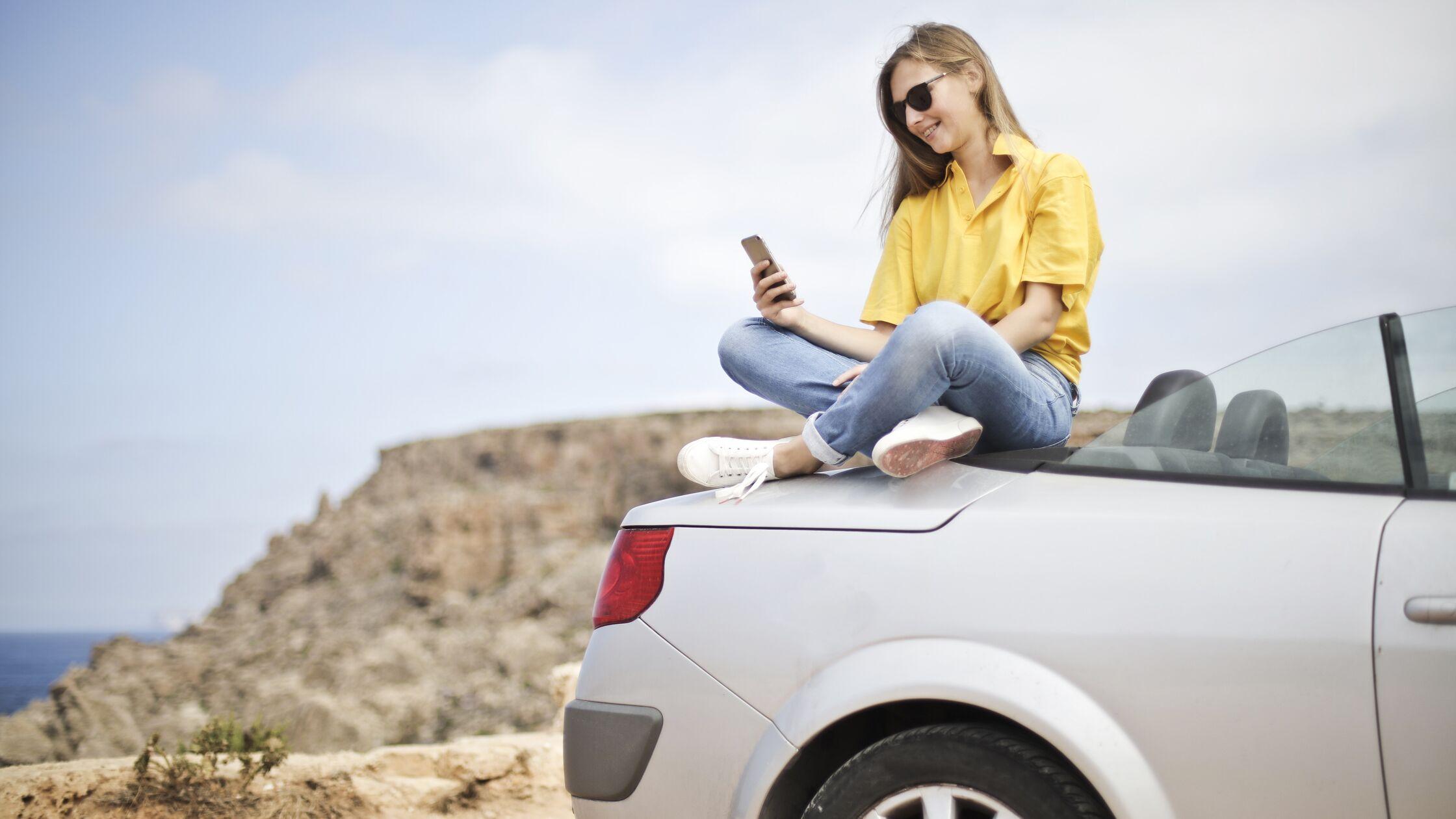 Junge Frau sitzt auf einem Auto und schaut aufs Handy
