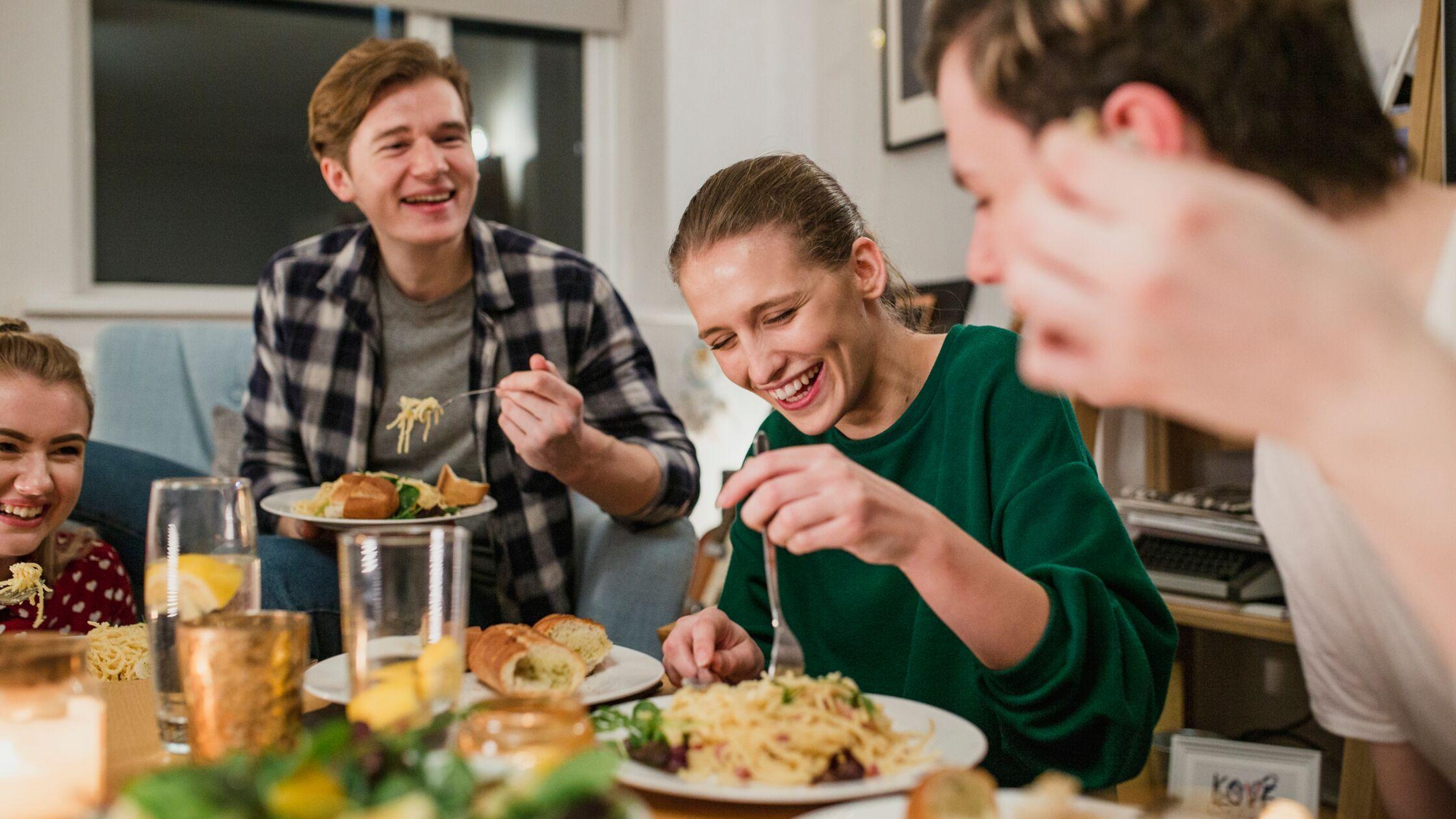 Lachende junge Leute kochen und essen zusammen