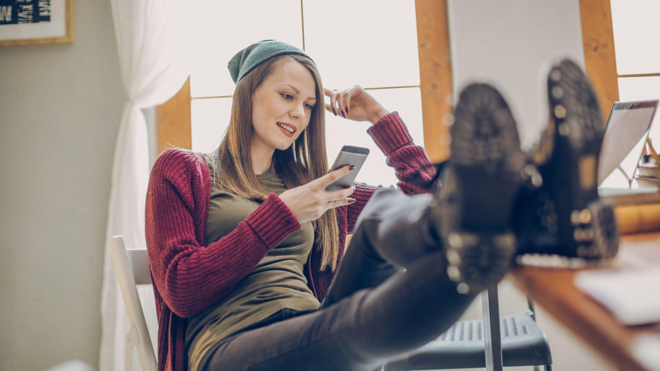 Zufriedene Studentin sitzt gemütlich am Schreibtisch