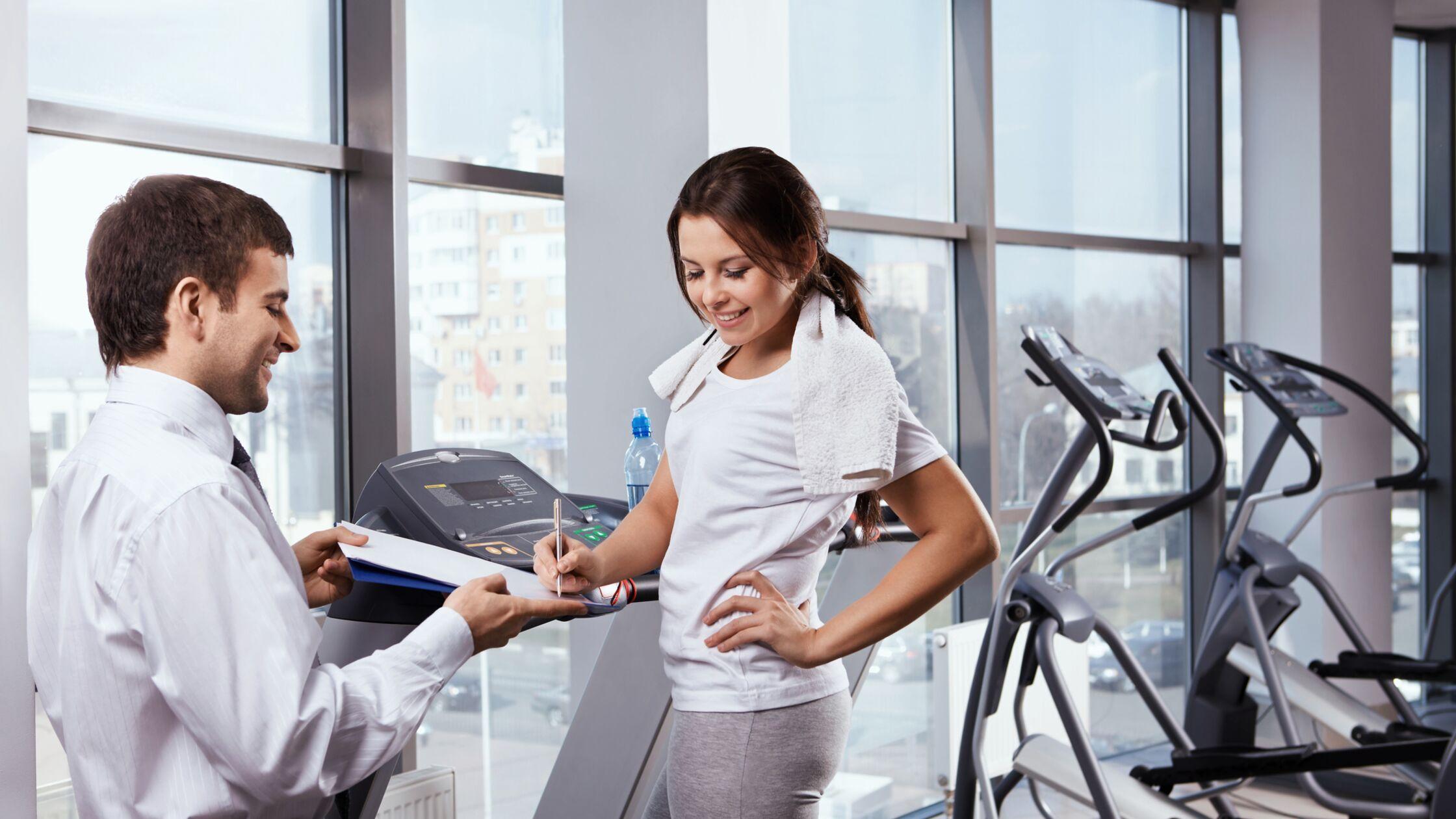 Junge Frau trainiert im Fitnessstuidion und unterschreibt ein Dokument