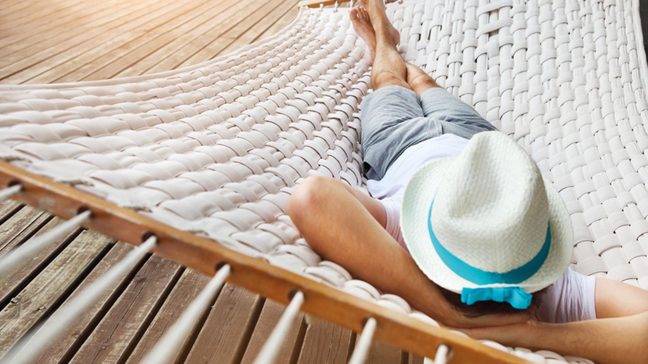 Mann mit Hut liegt in einer Hängematte