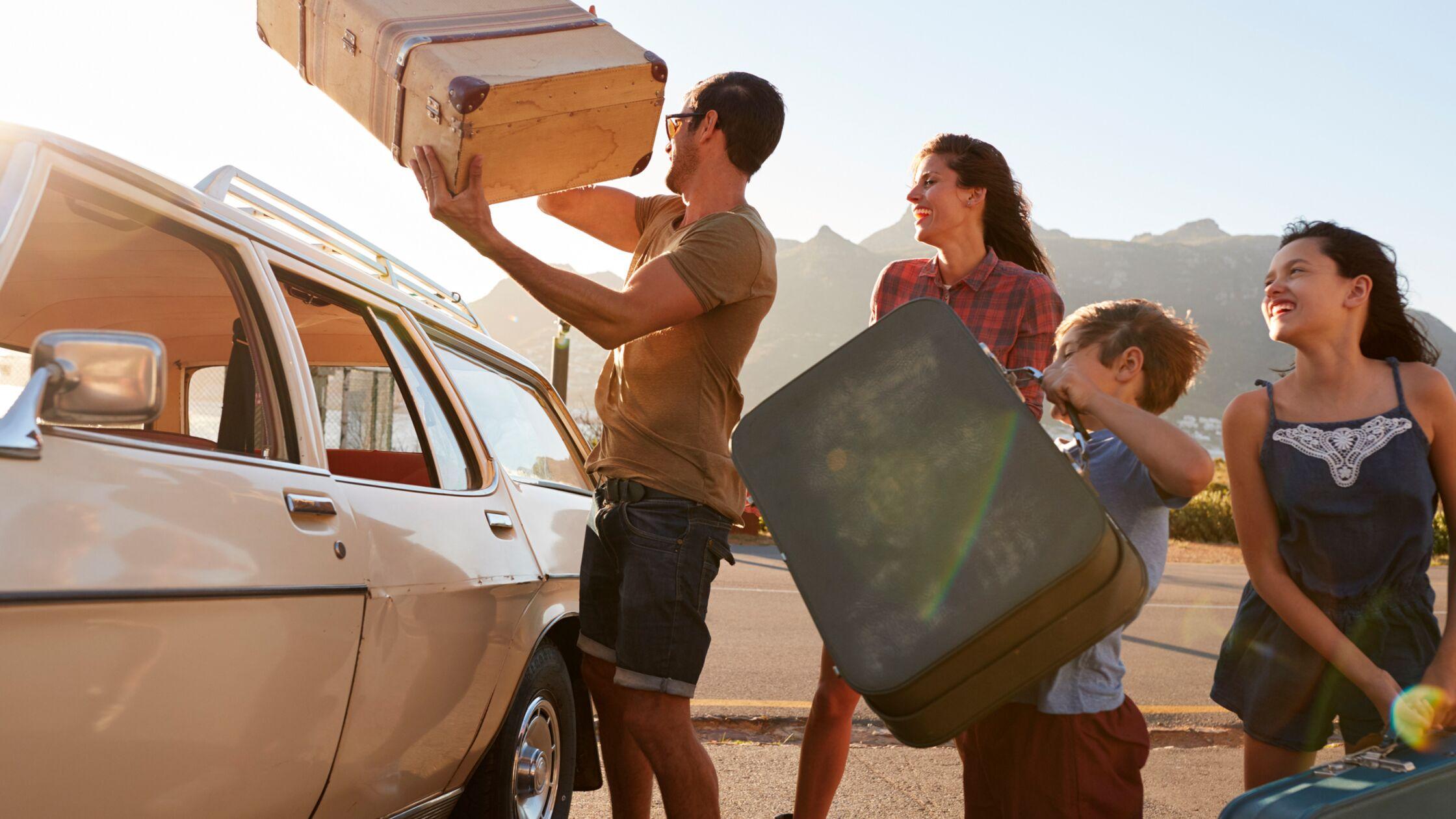 Familie lädt Koffer ins Auto