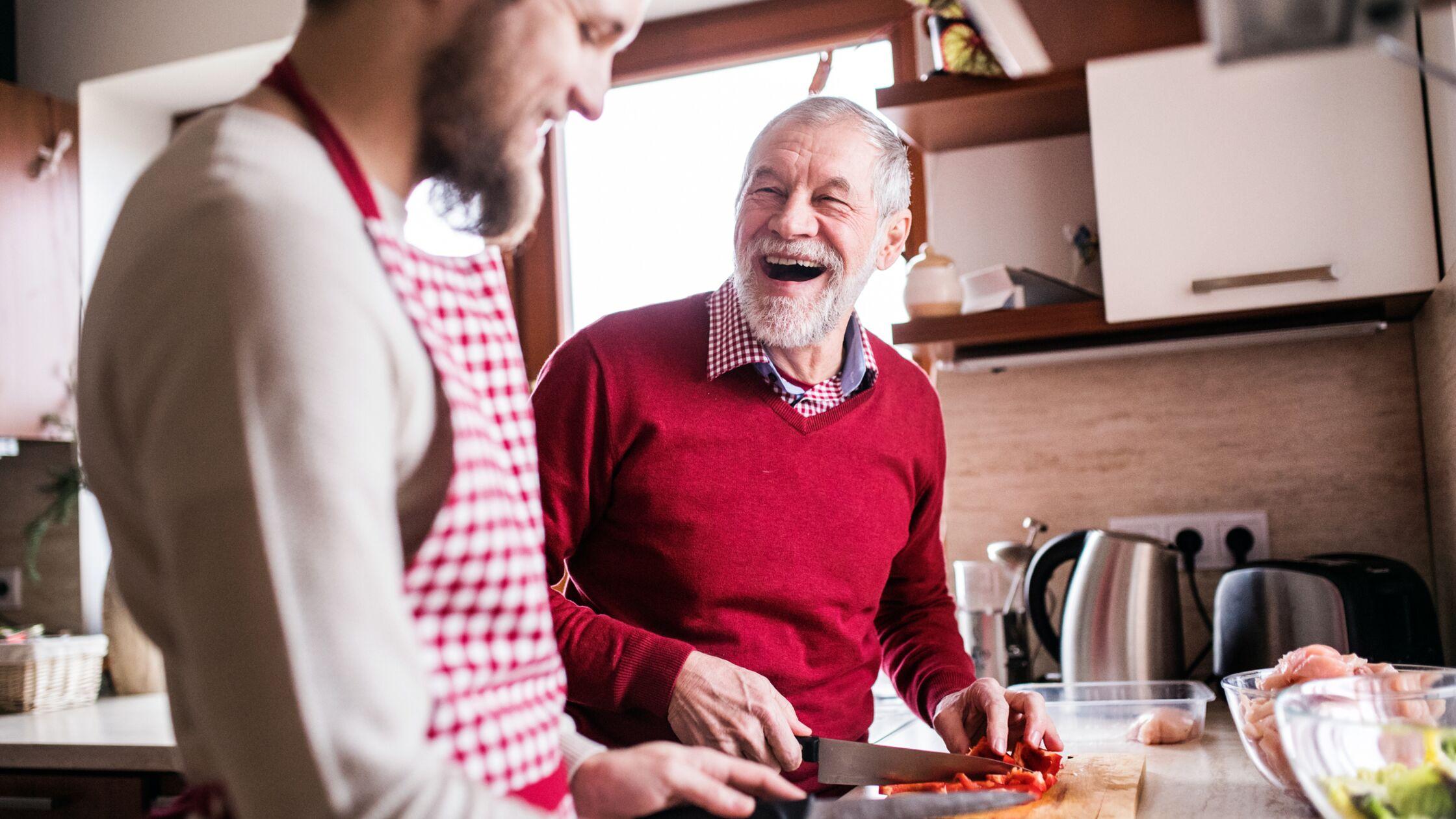 Junger und älterer Mann kochen gemeinsam
