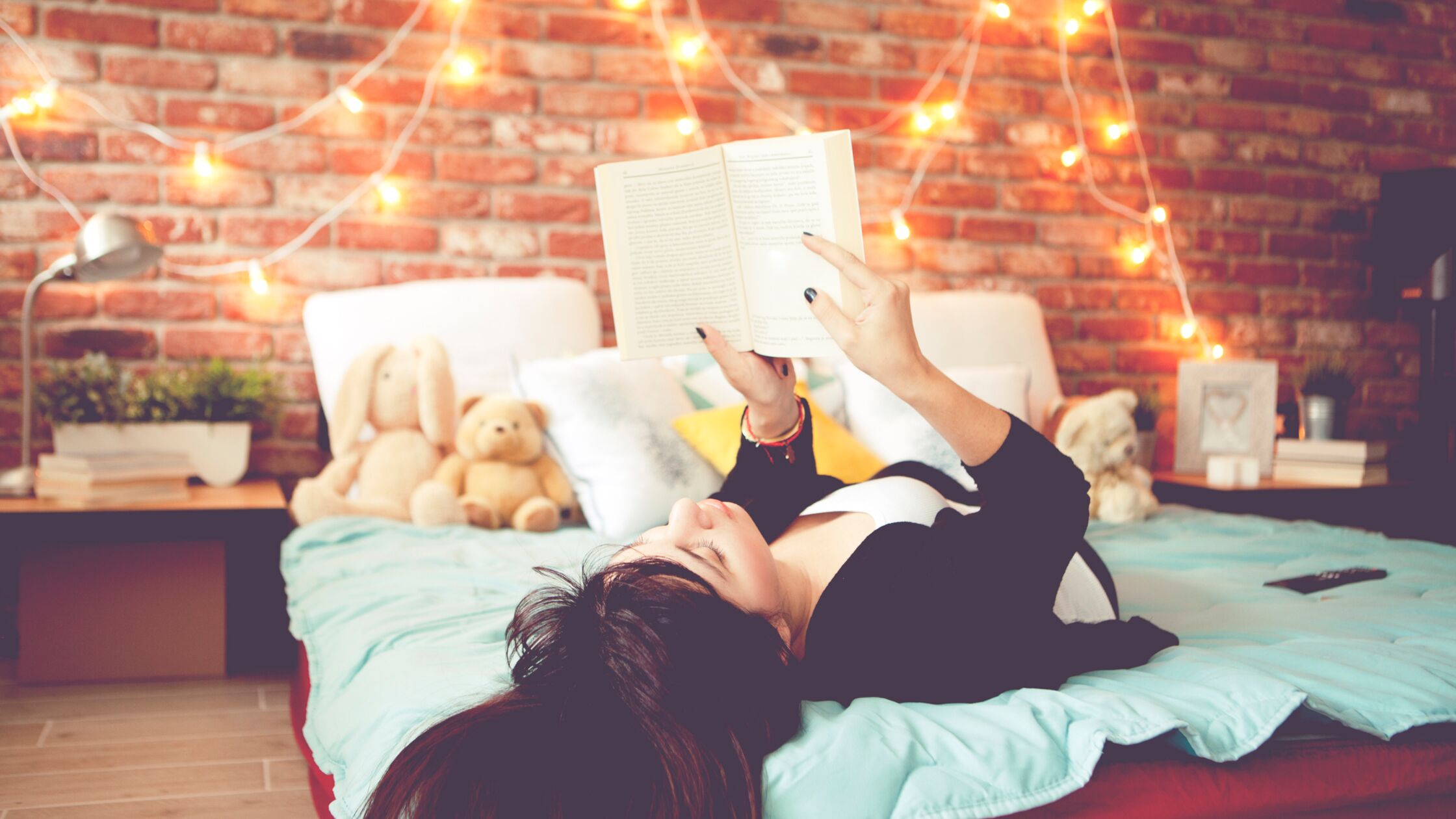 Frau liegt auf einem Jugendzimmer-Bett und liest