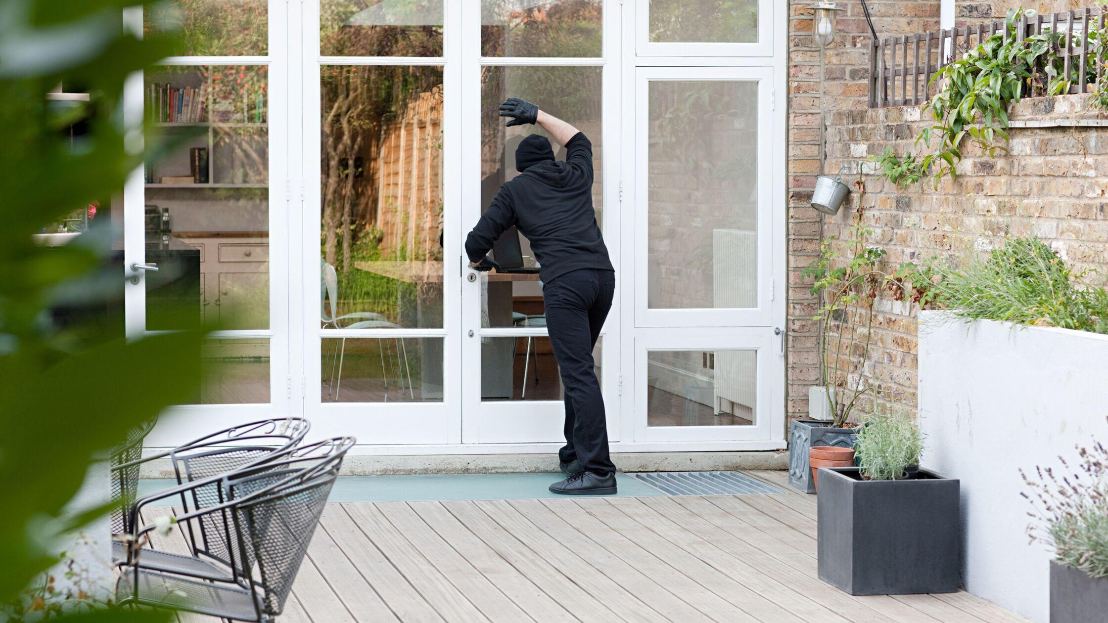 Einbrecher steht vor einer Terrassentür und schaut nach drinnen