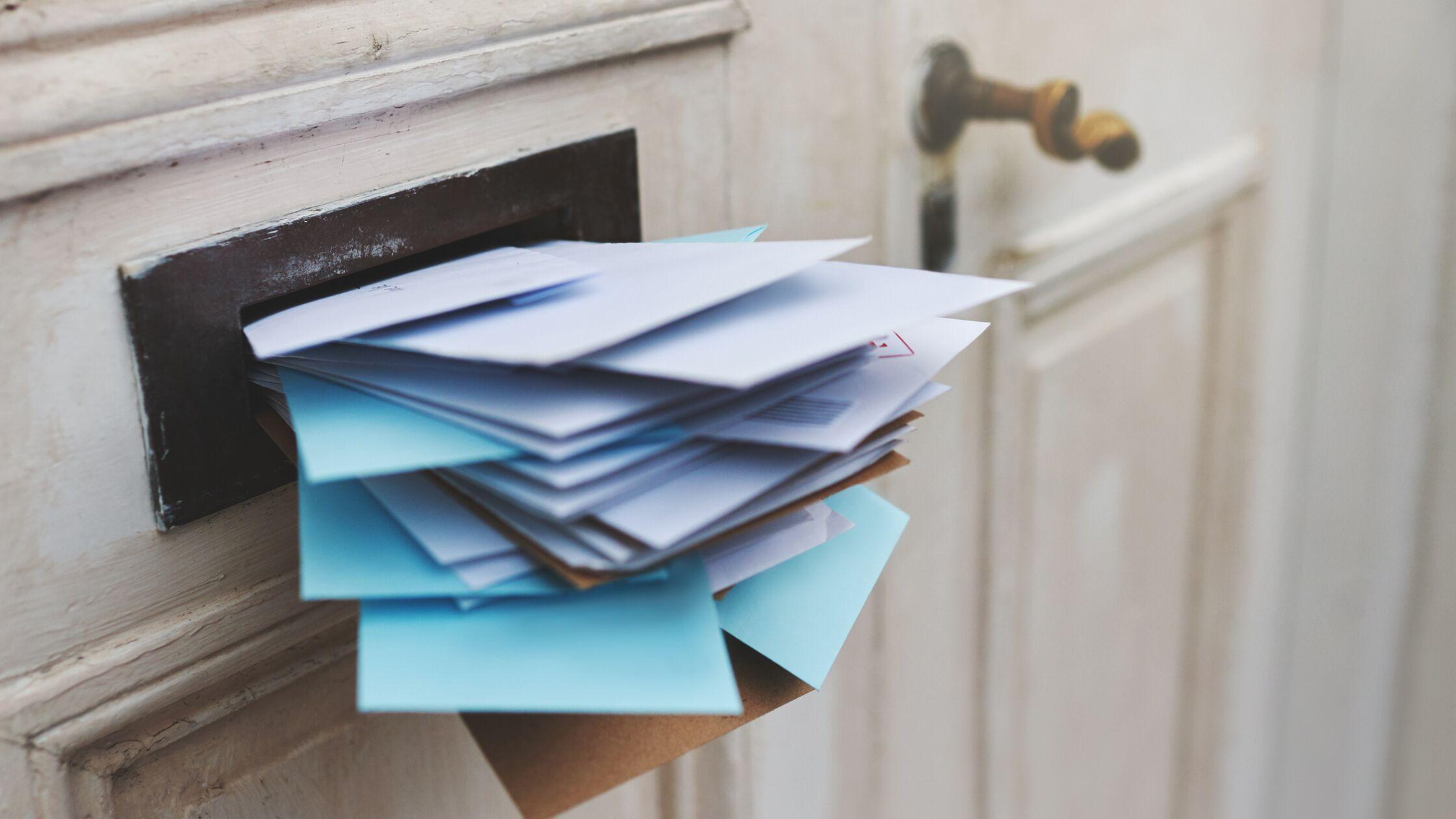 Briefschlitz in einer Wohnungstür, vollgestopft mit Briefen