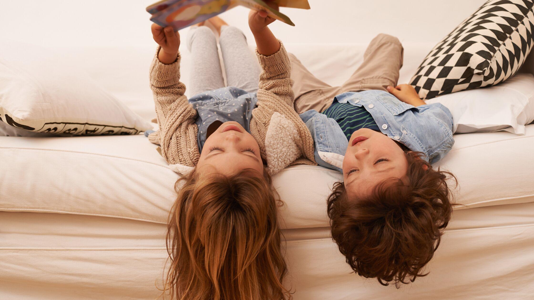 Zwei Kinder liegen auf einem Bett und lesen ein Buch