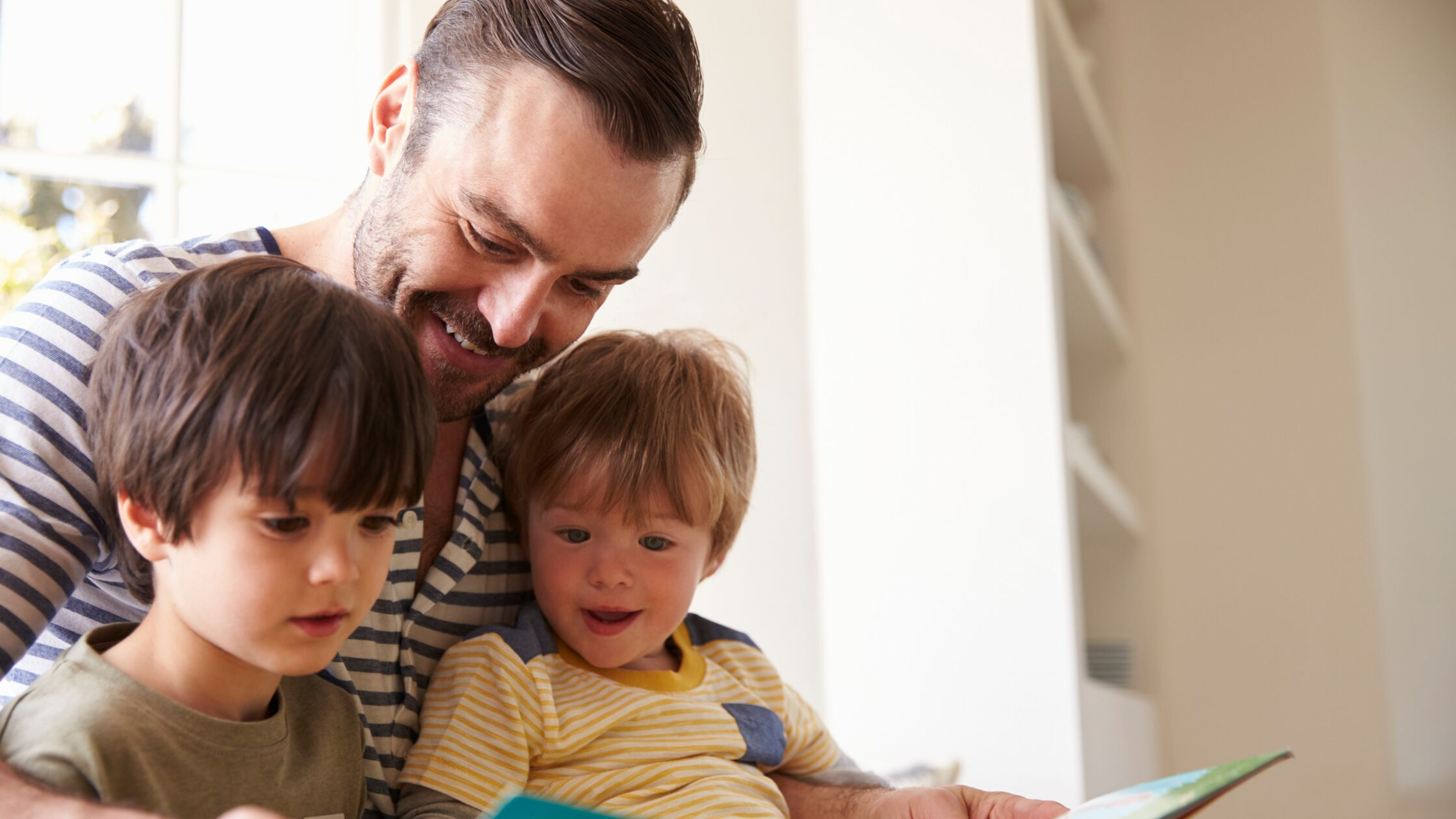 Vater liest seinen zwei Söhnen ein Buch vor
