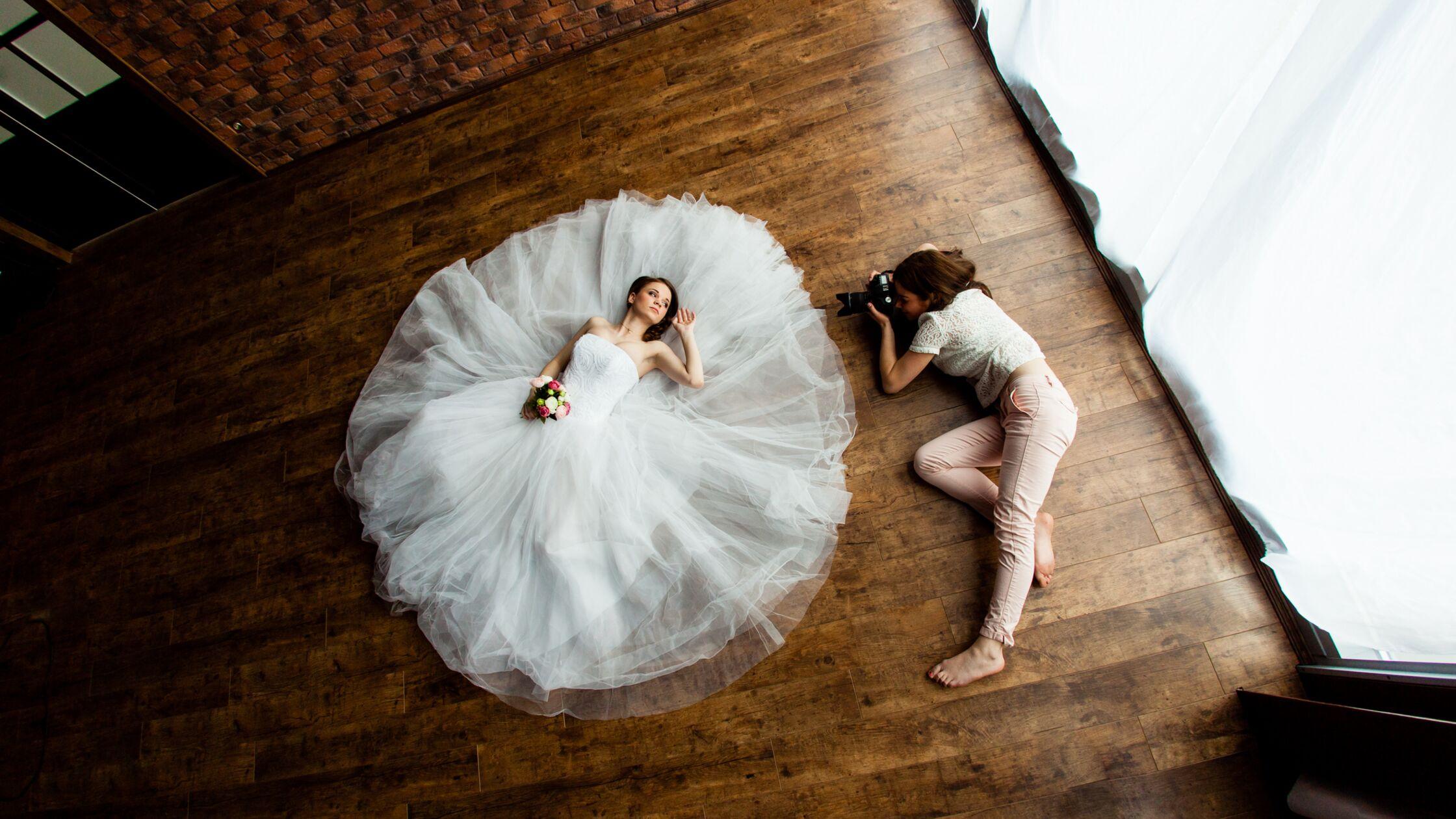 Fotografin und und Model beim Brautshooting auf dem Fußboden in einer leeren Wohnung