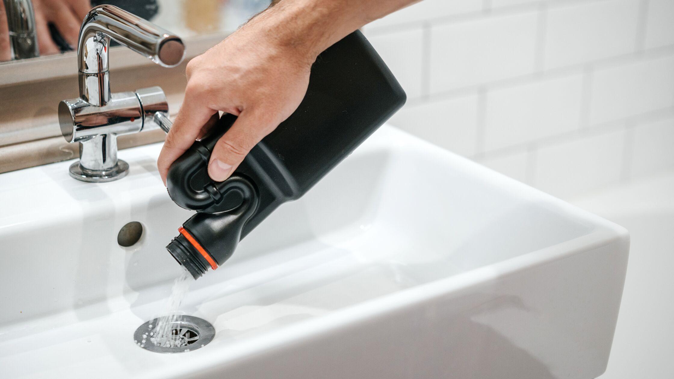 Mann schüttet Rohrreiniger in den Ausguss eines Waschbeckens