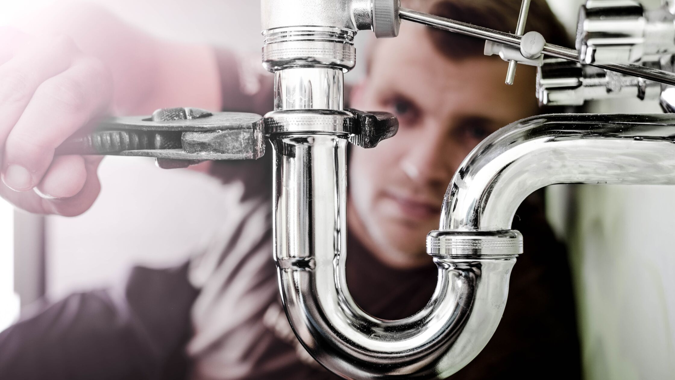 Mann schraubt mit einer Zange den Metallsiphon eines Waschbeckens ab