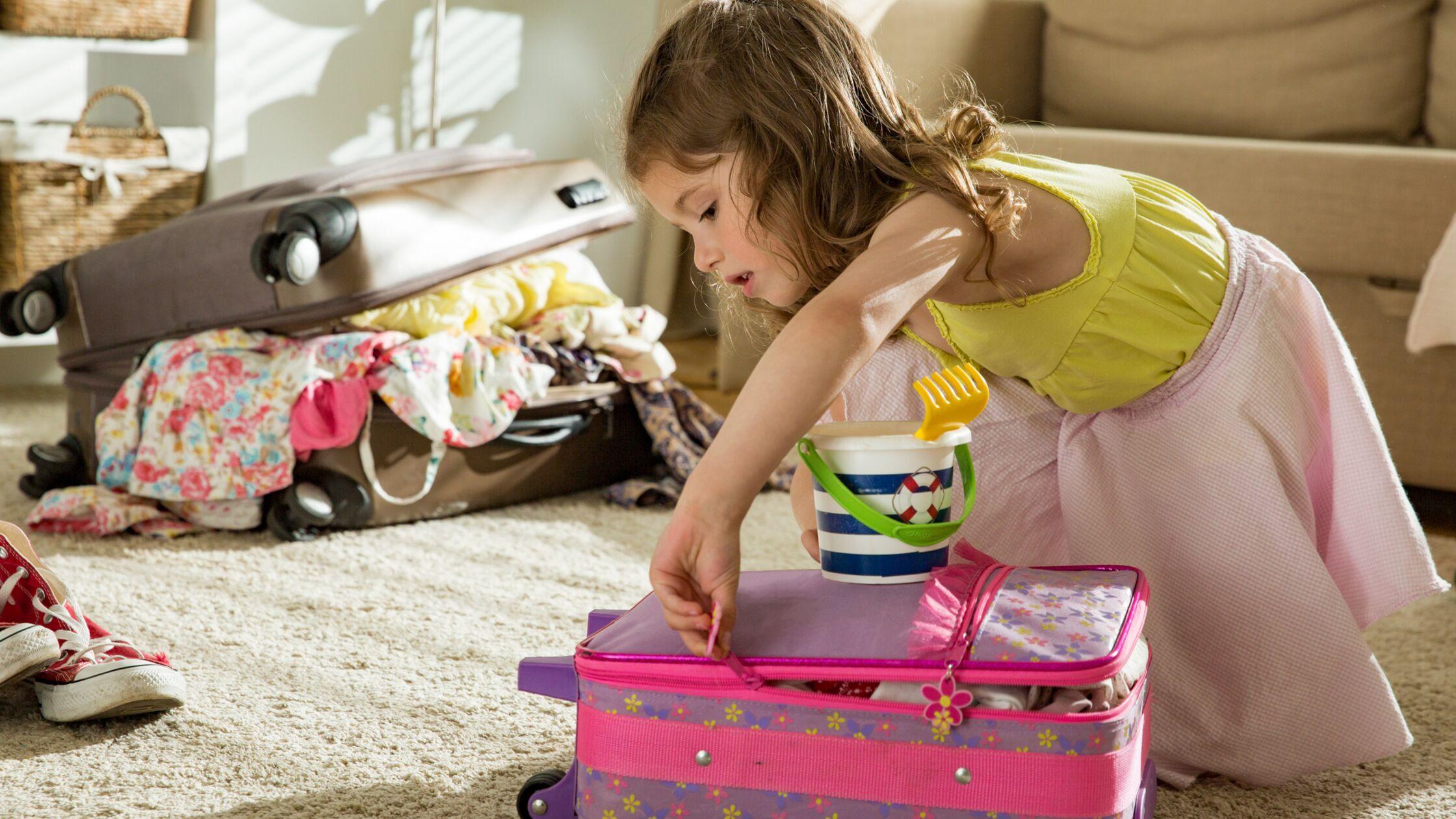 Kleines Mädchen packt Reisekoffer