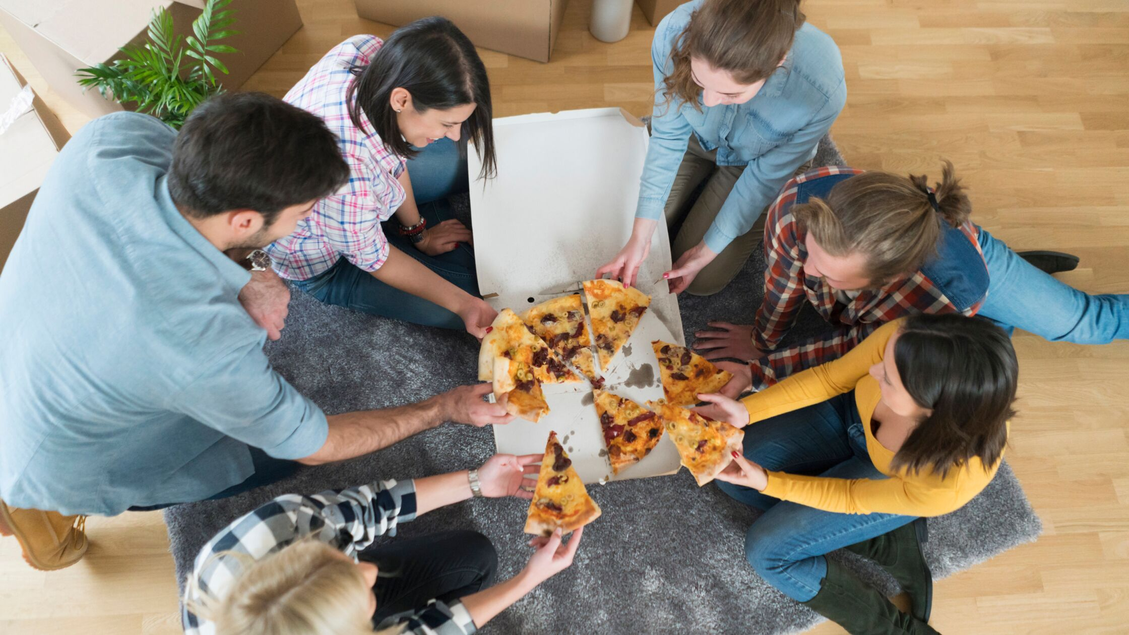 Gruppe von jungen Leuten sitzt zwischen Umzugskartons und teilt sich eine Pizza