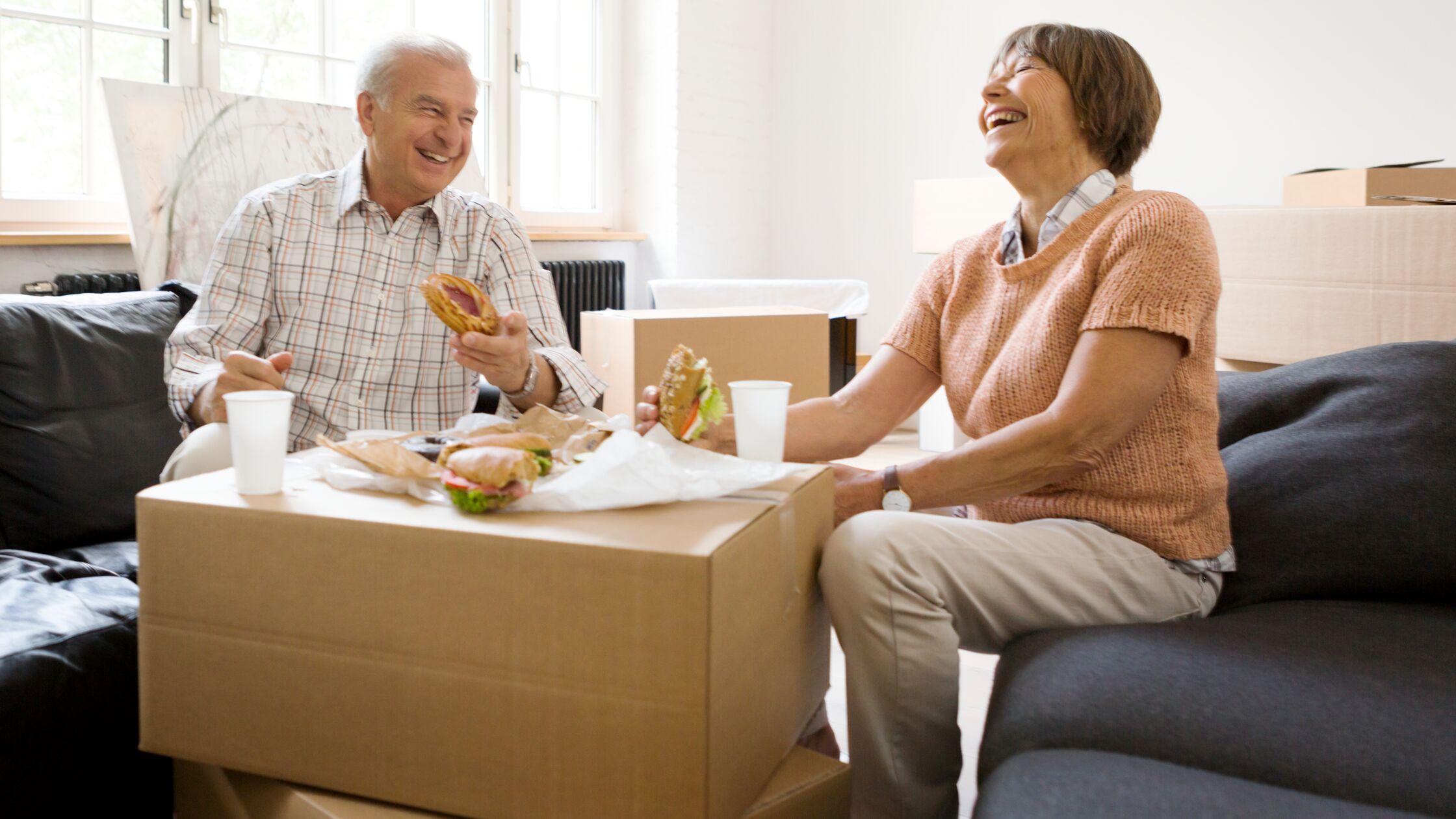 Älteres Paar sitzt zwischen Umzugskartons, darauf belegte Brote.