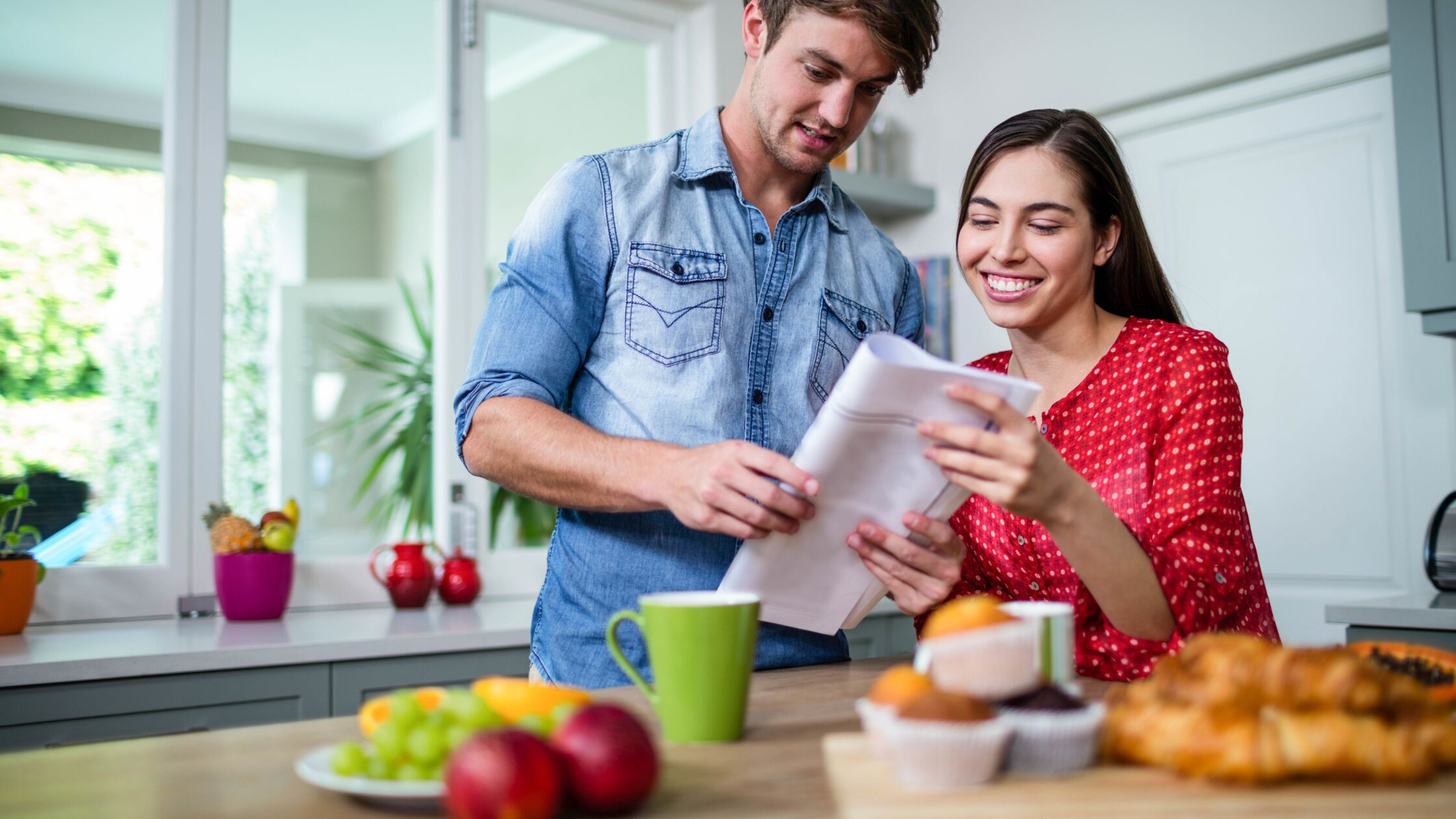 Happy couple having breakfast and reading newspaper at home