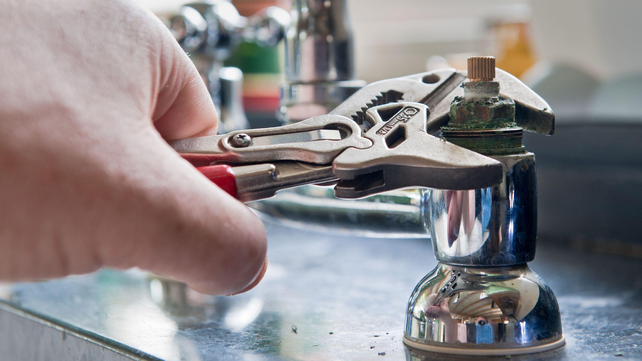 Hand mit Wasserpumpenzange schraubt an einem Wasserhahnventil