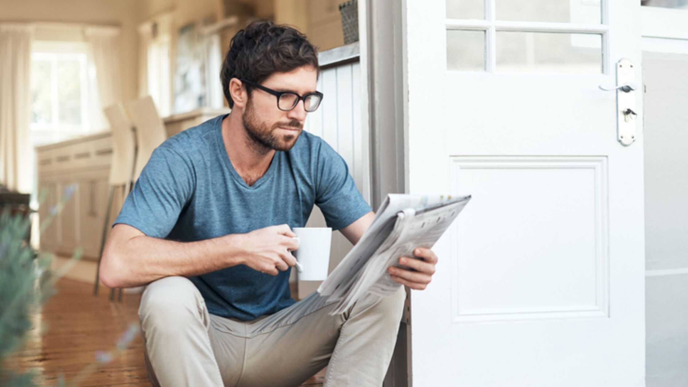 Mann liest Zeitung auf der Türschwelle