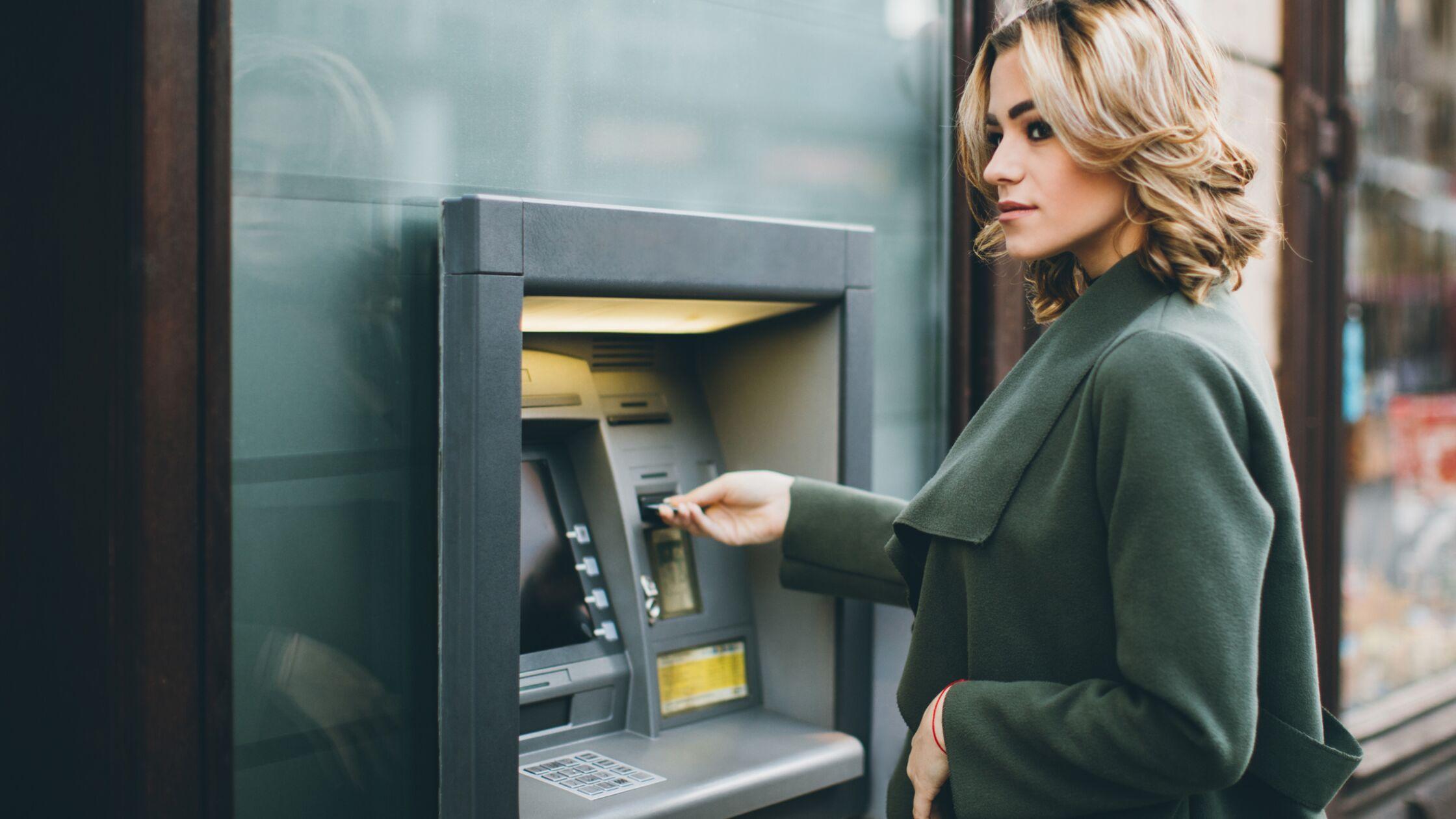 Frau steht am Geldautomaten