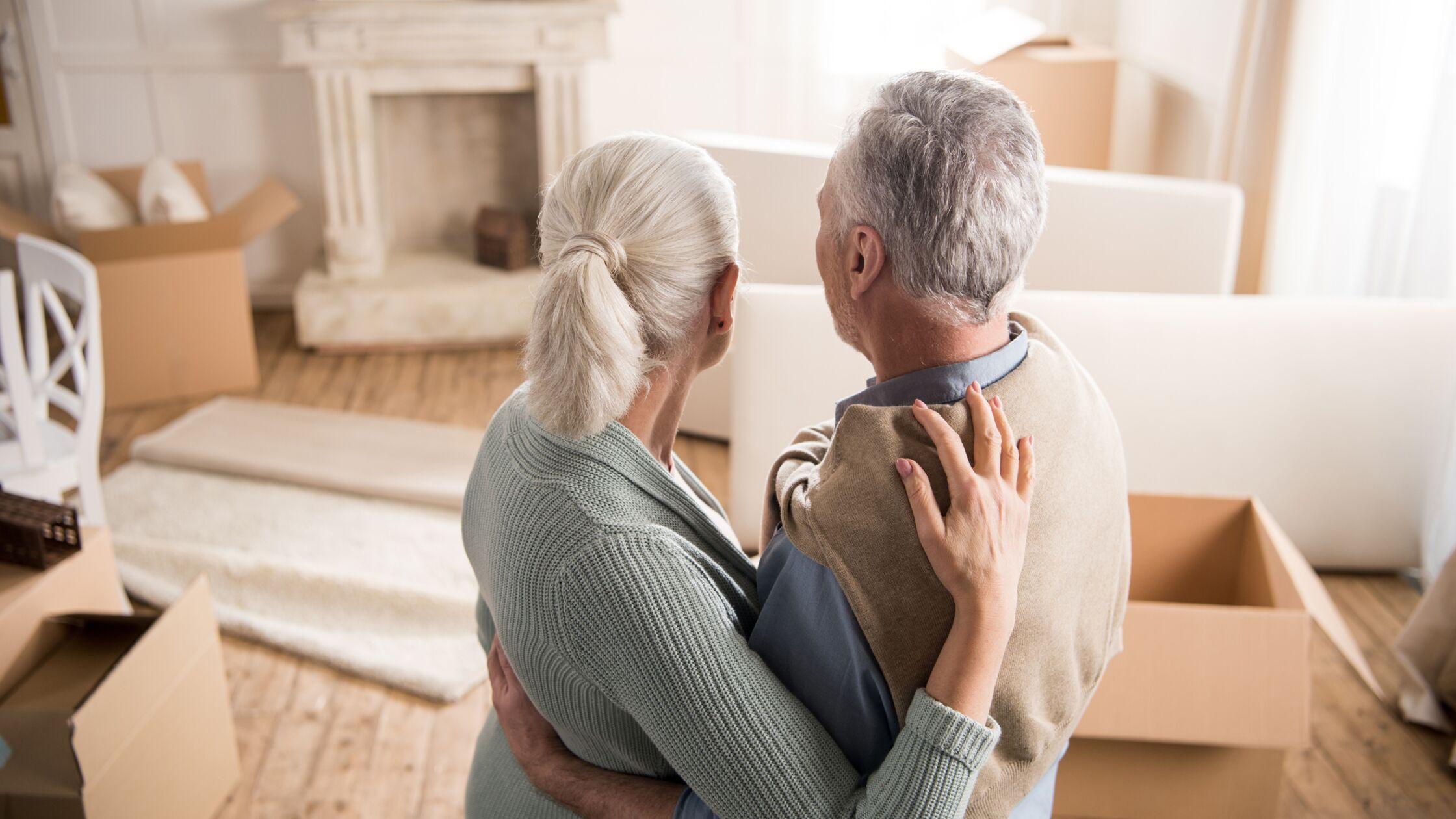 Älteres Paar umarmt sich und blickt auf ausgeräumtes Haus