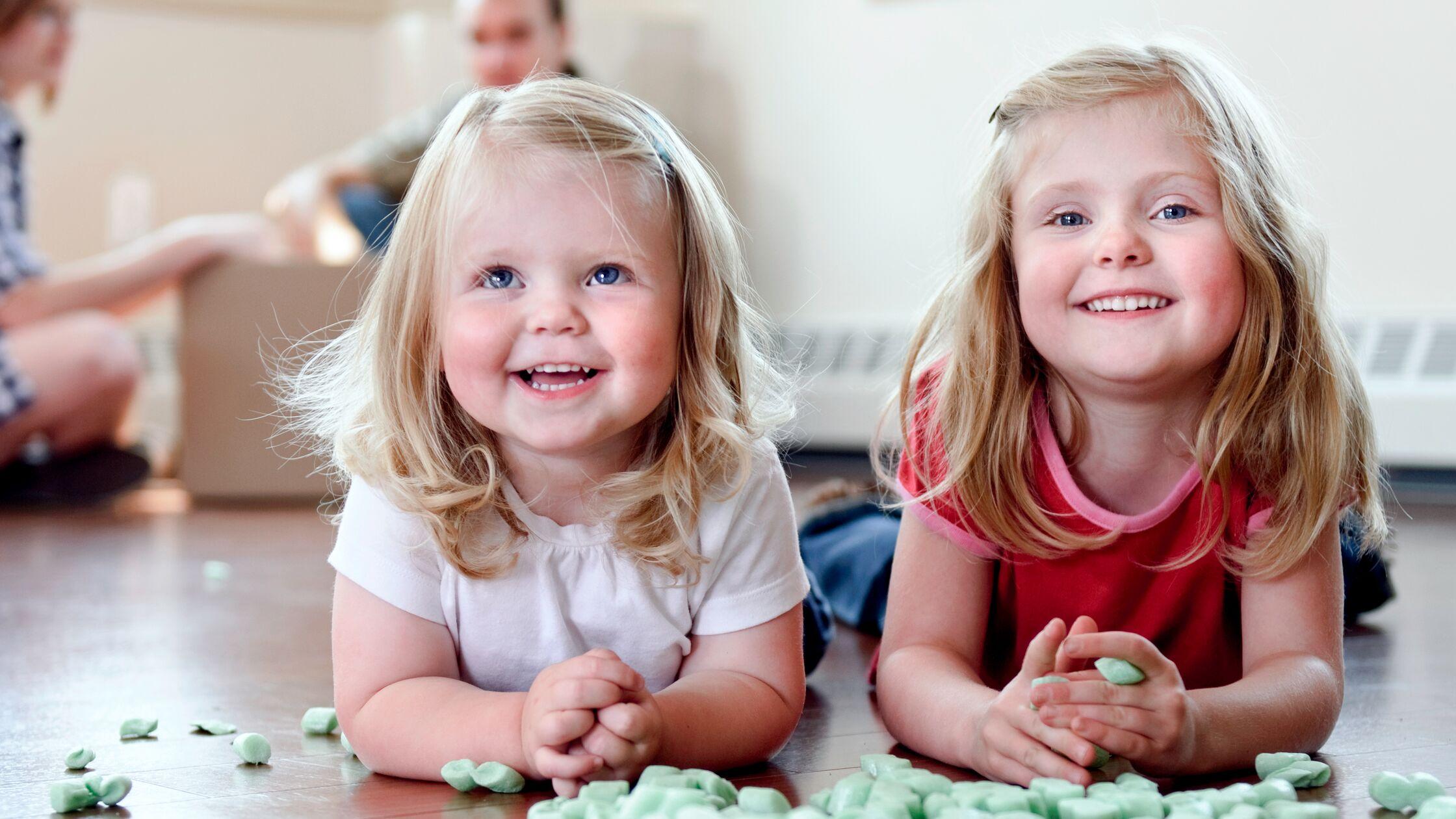 Kleine Mädchen spielen mit Verpackungsmaterial, im Hintergrund die Eltern mit