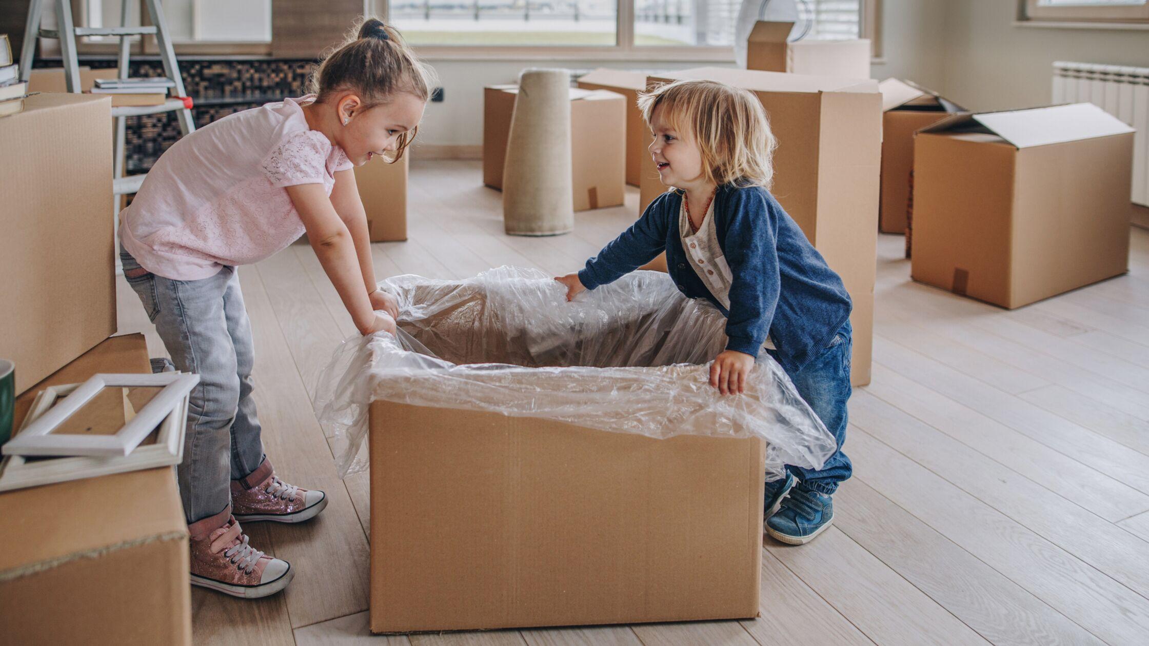 Mädchen und Junge mit einem Umzugskarton
