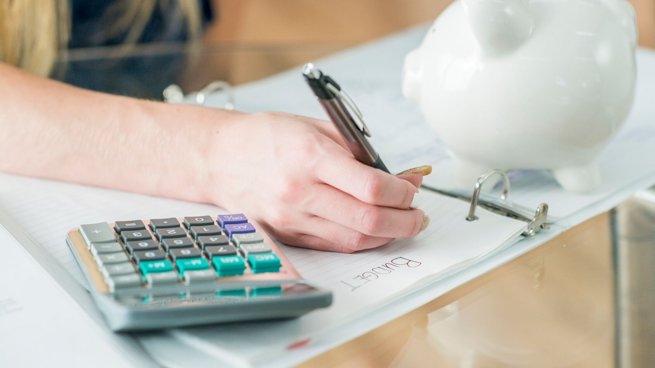 Hand einer Frau mit Taschenrechner, Schreibblock und Sparschwein.