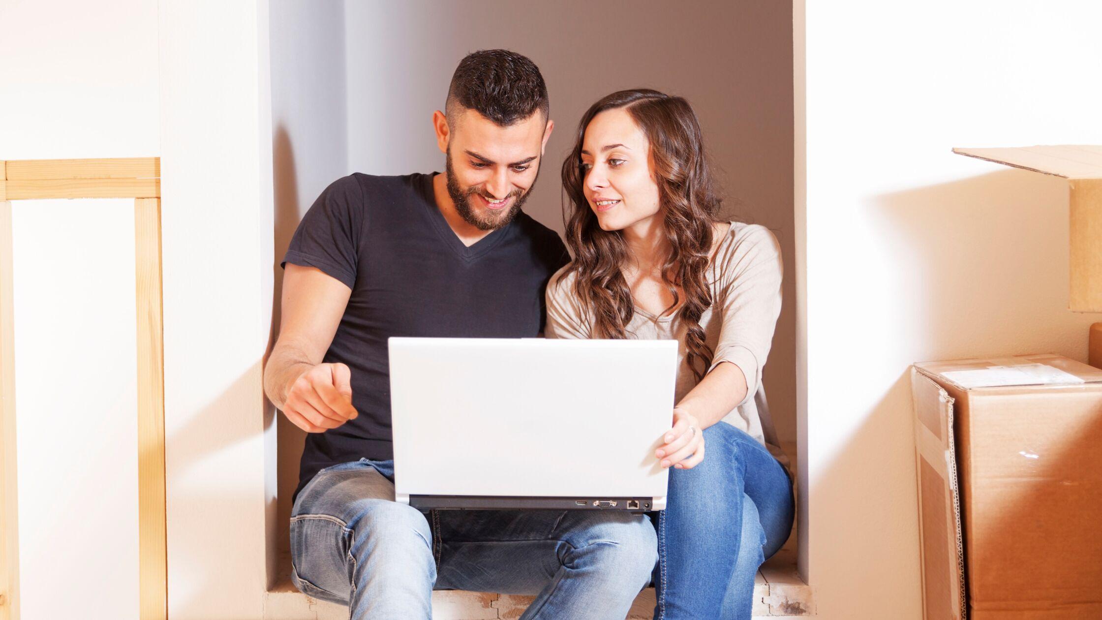 Junges Paar sitzt mit Laptop auf dem Schoß zwischen Umzugskisten