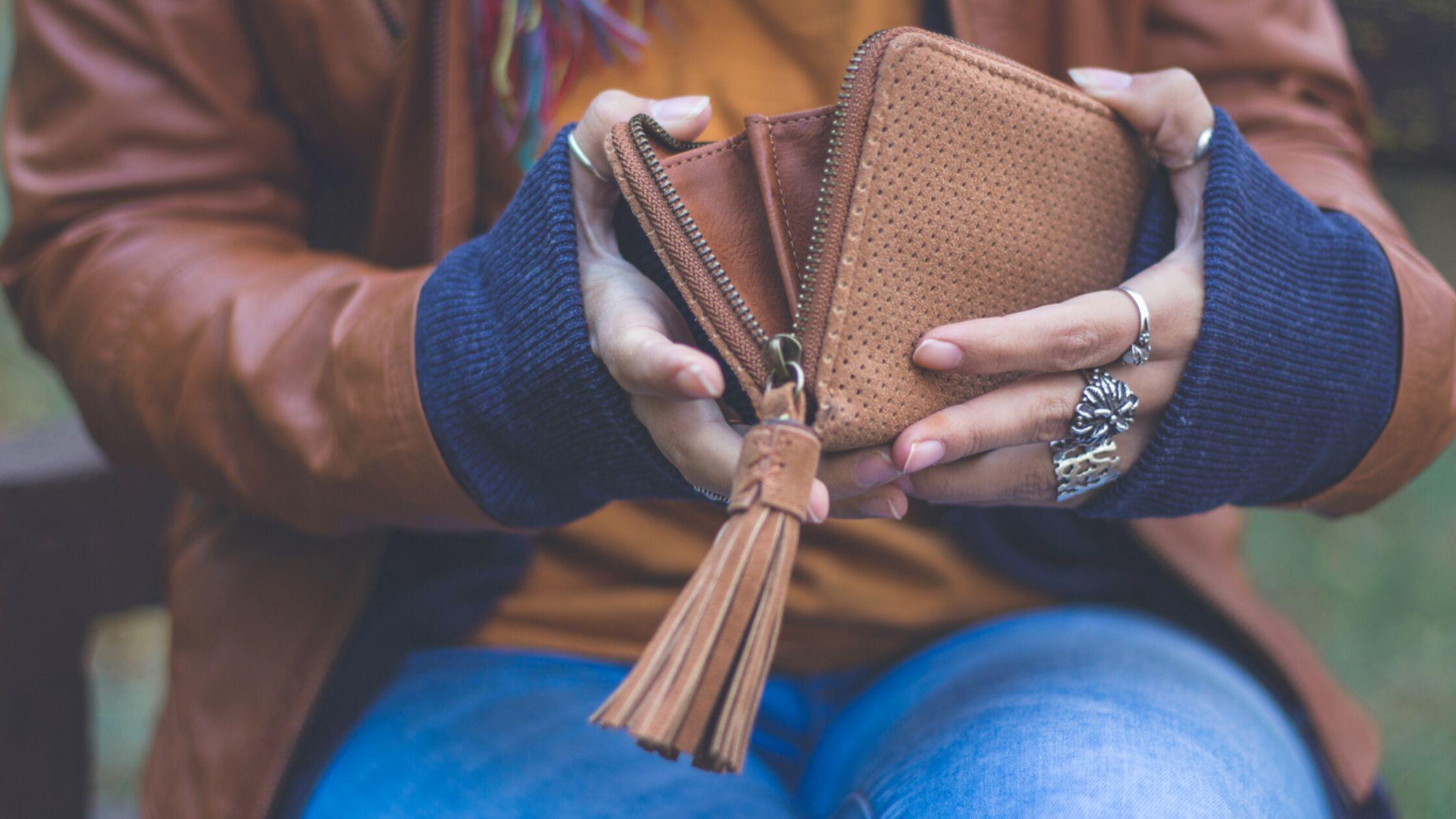 Frau öffnet Geldbörse