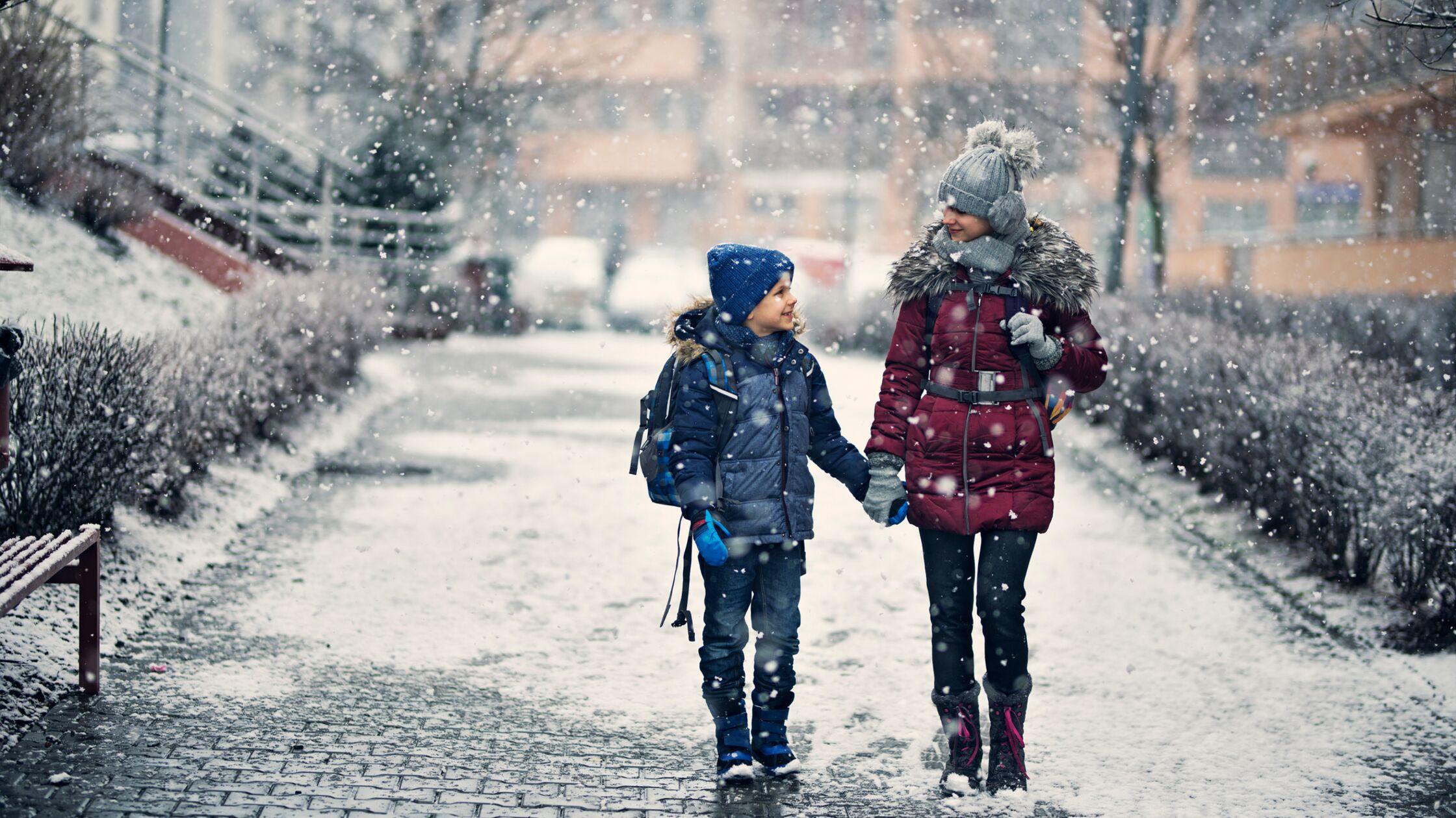 Geschwisterpaar spaziert im Winter über geräumten Gehweg